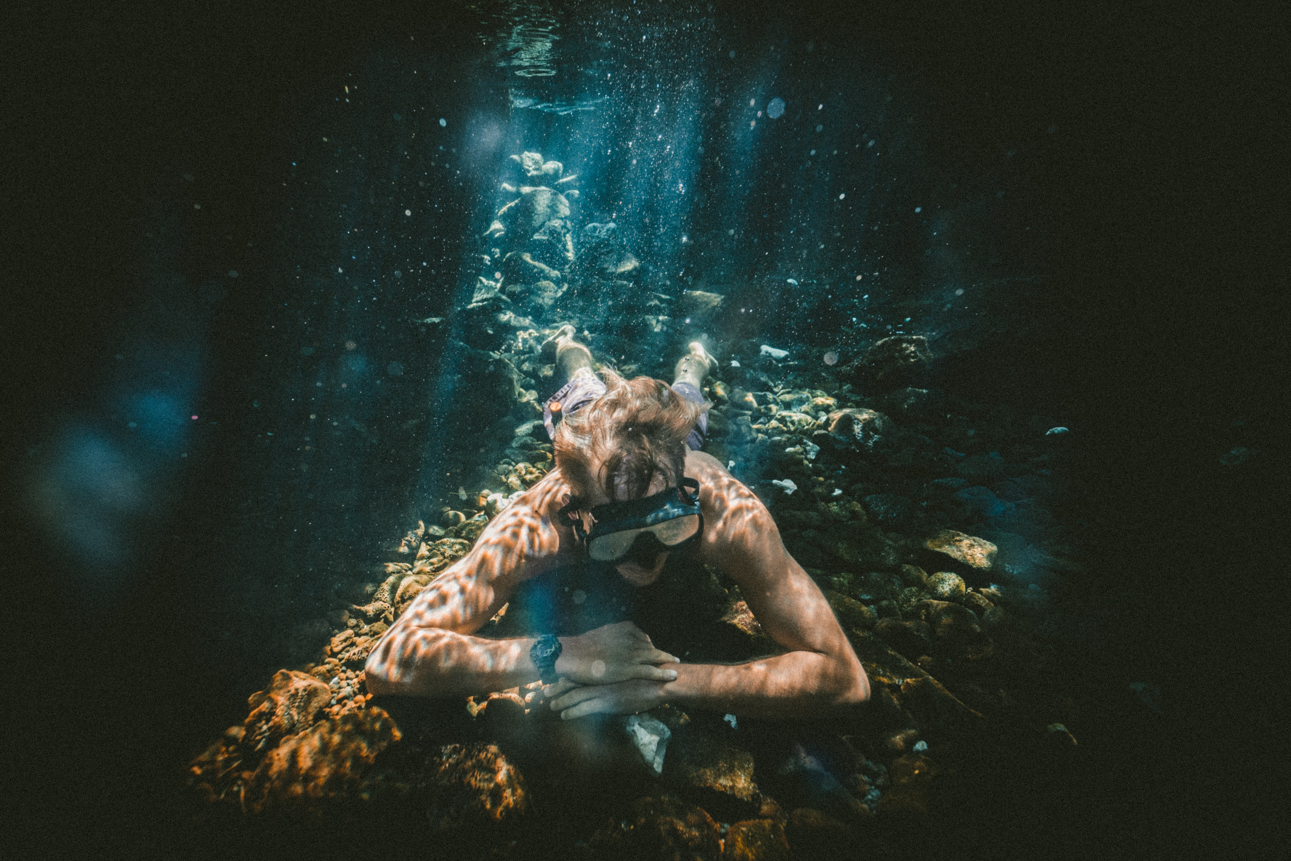 An underwater photo of a man snorkeling in a cave in the ocean