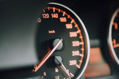 closeup photo of black analog speedometer car teams background