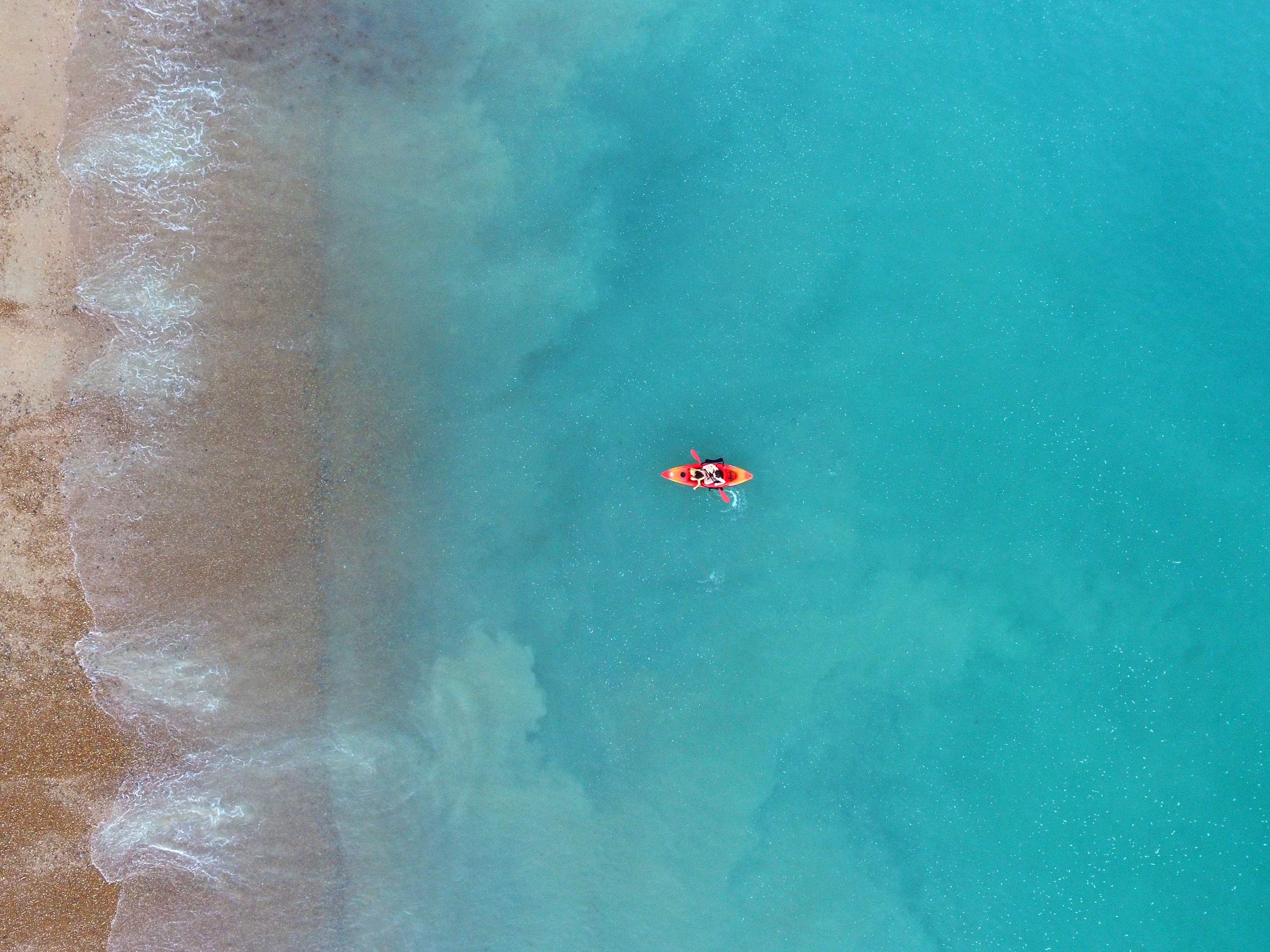 A drone view of a person kayaking in the sea in Brighton