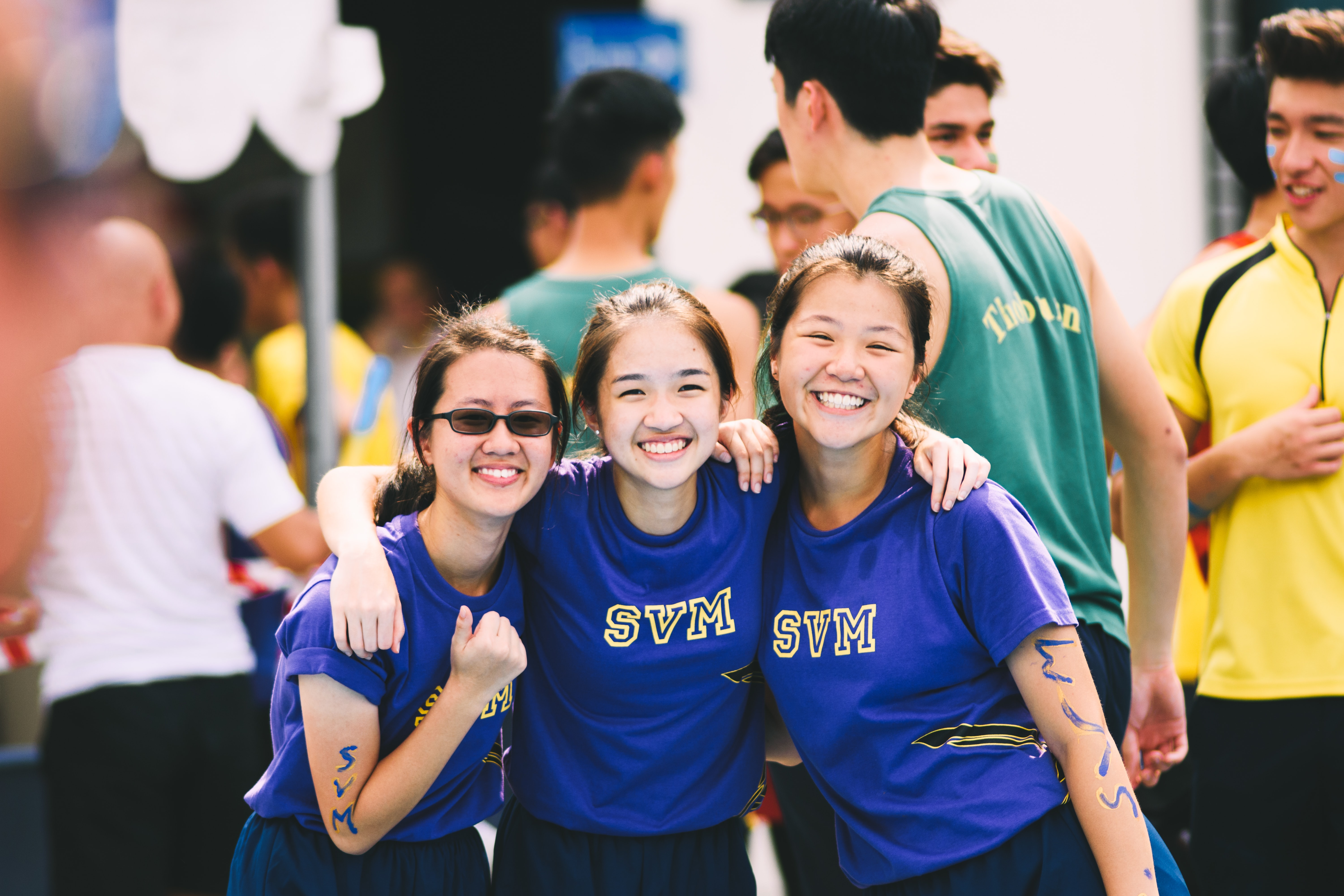 Group of female students excitedly smiling at the camera during a sports event