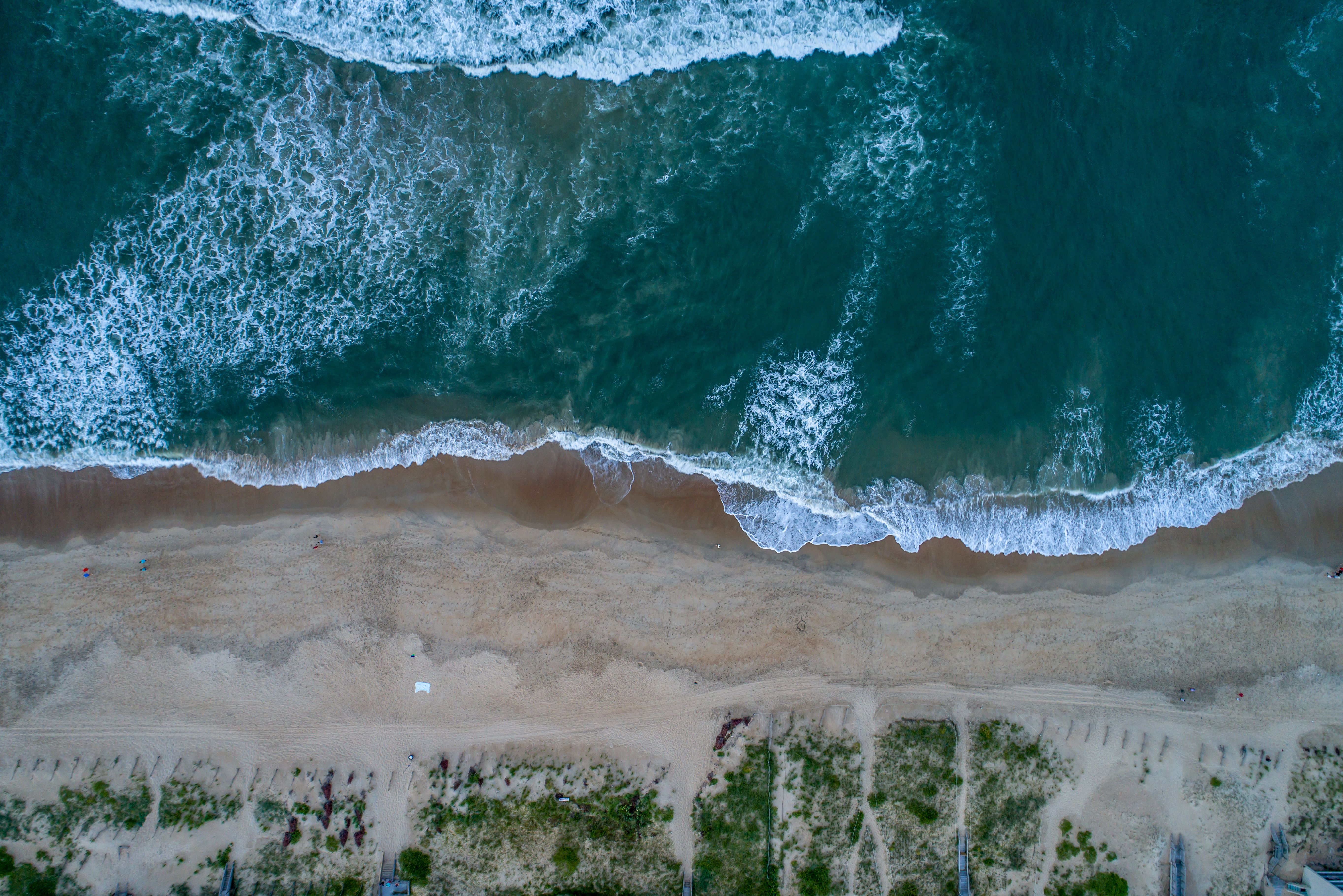 Drone view of the ocean washing on a sand shoreline at Nags Head, North Carolina, United States