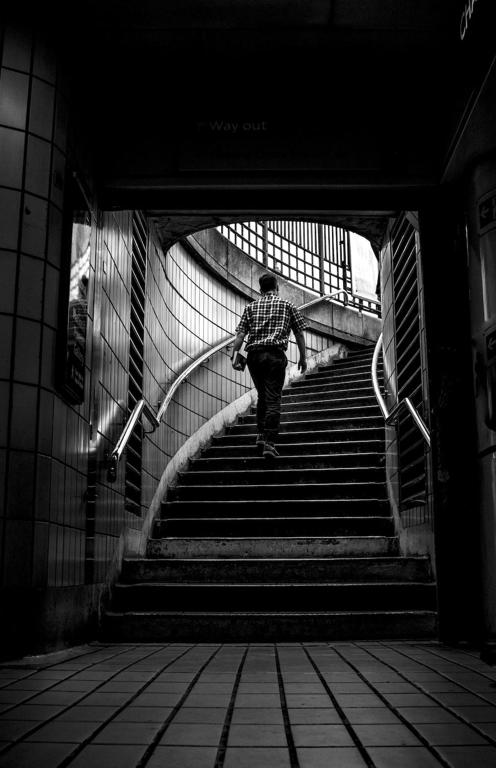 grayscale photo of man walking upstairs