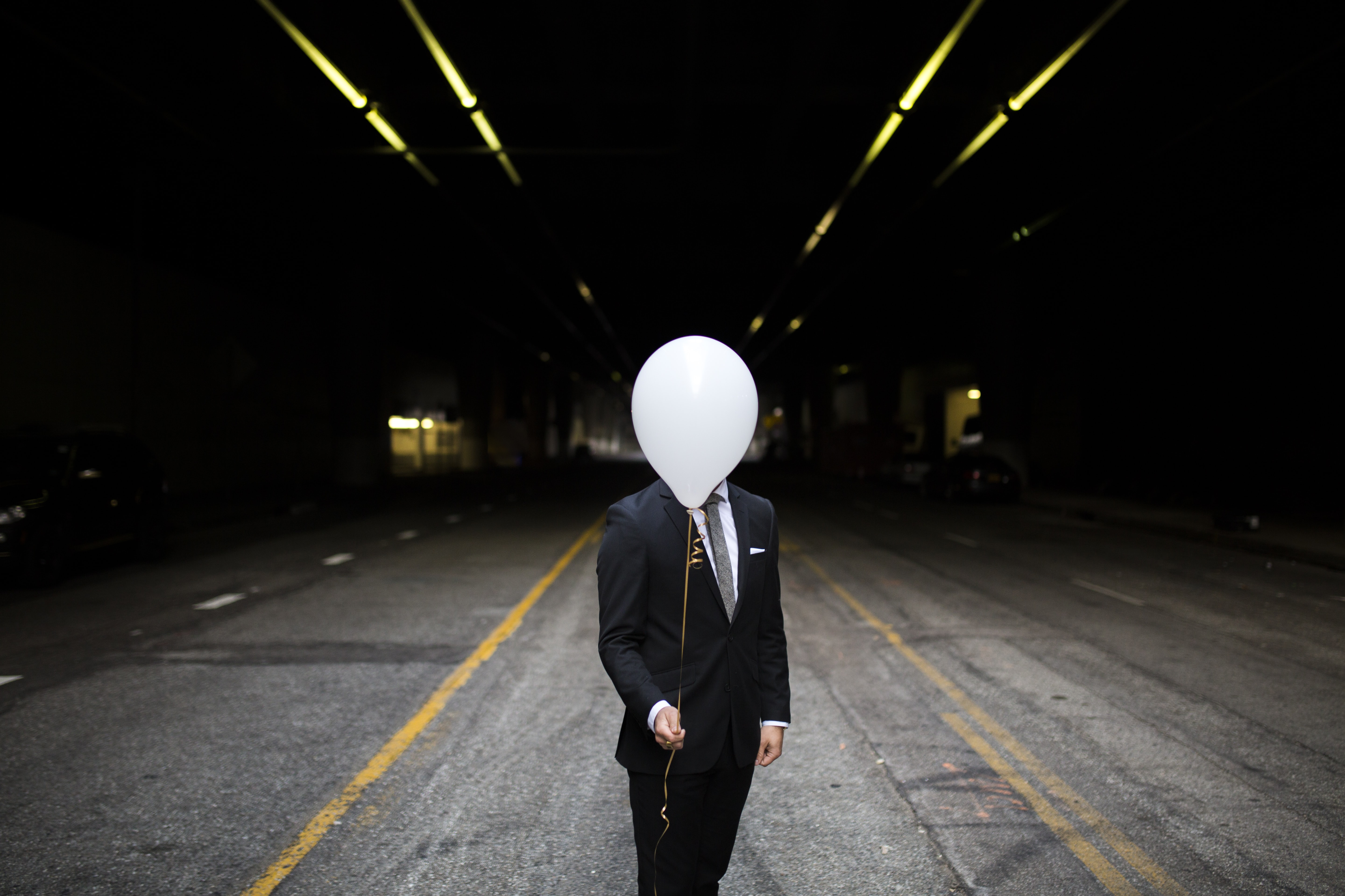 A man in a dark suit holding with a white balloon obscuring his face