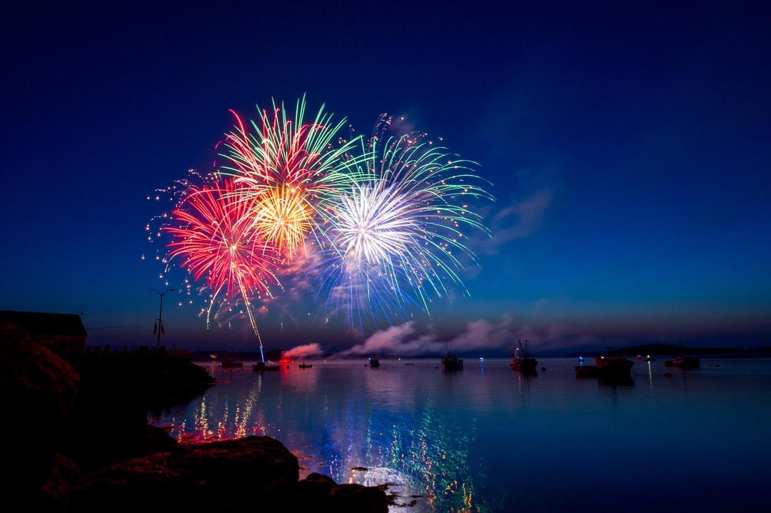 A fireworks display in the harbor of Lubec Maine.  The dusk sky, water and boats provided a beautiful setting for the colorful show.
