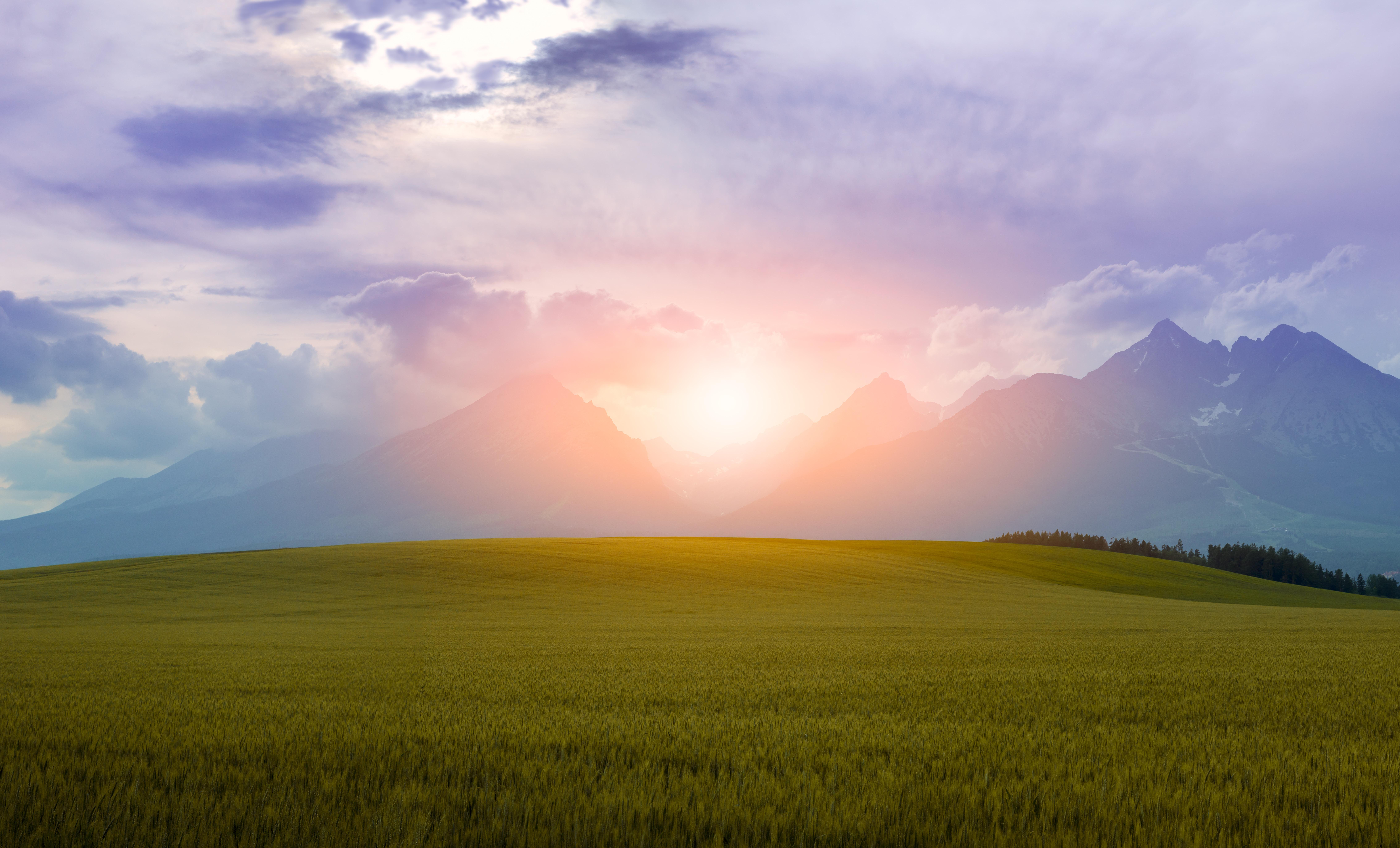 green grass field near mountains under cloudy sky during daytime