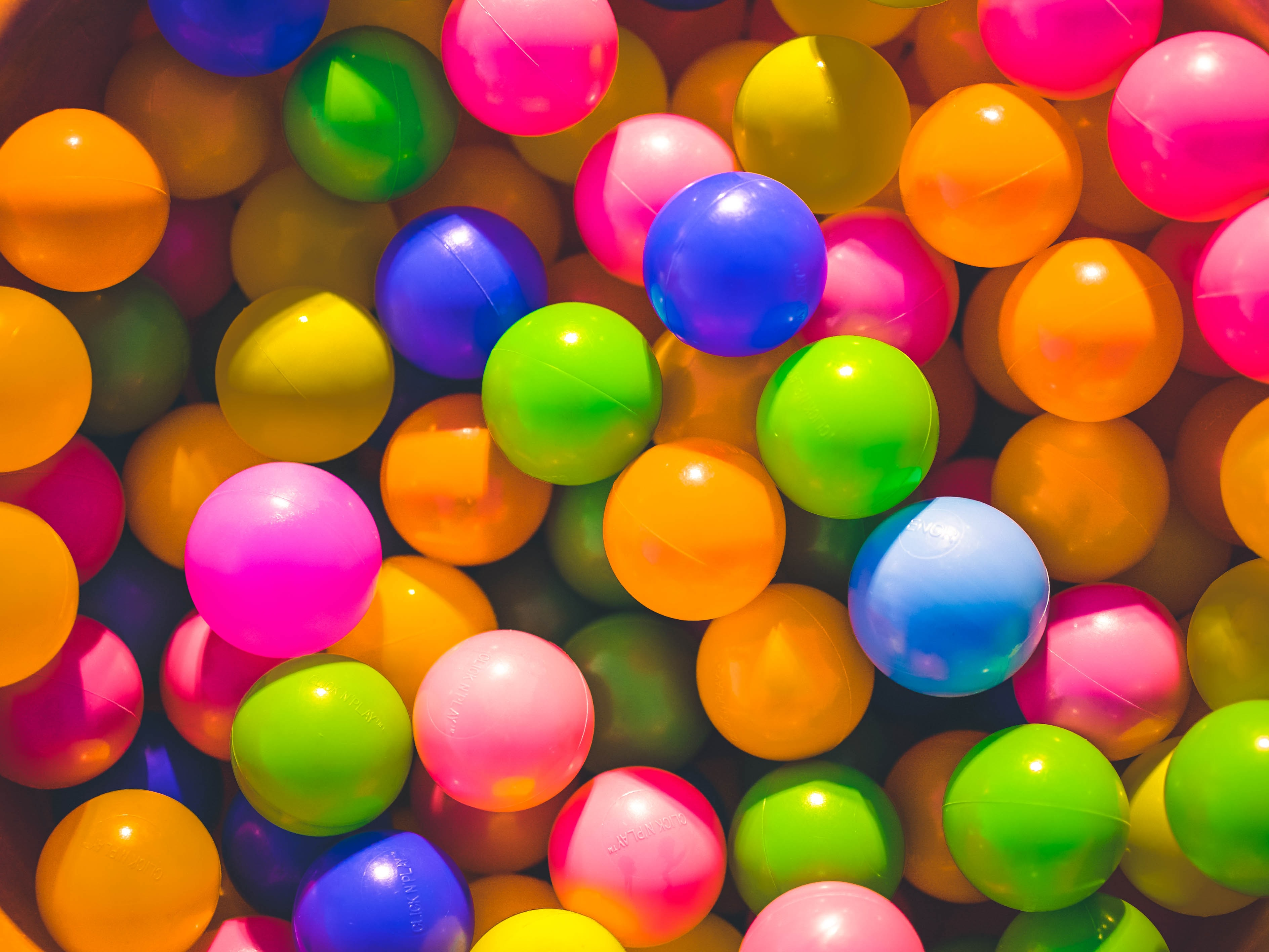 A bunch of colorful balls inside of a ball pit for little kids