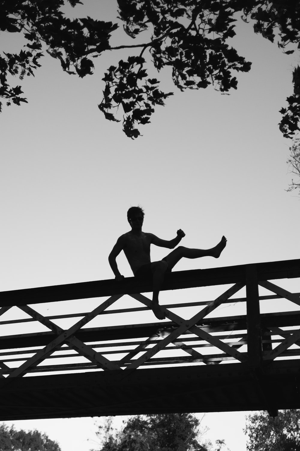 silhouette photo of a man about to jump on footbridge