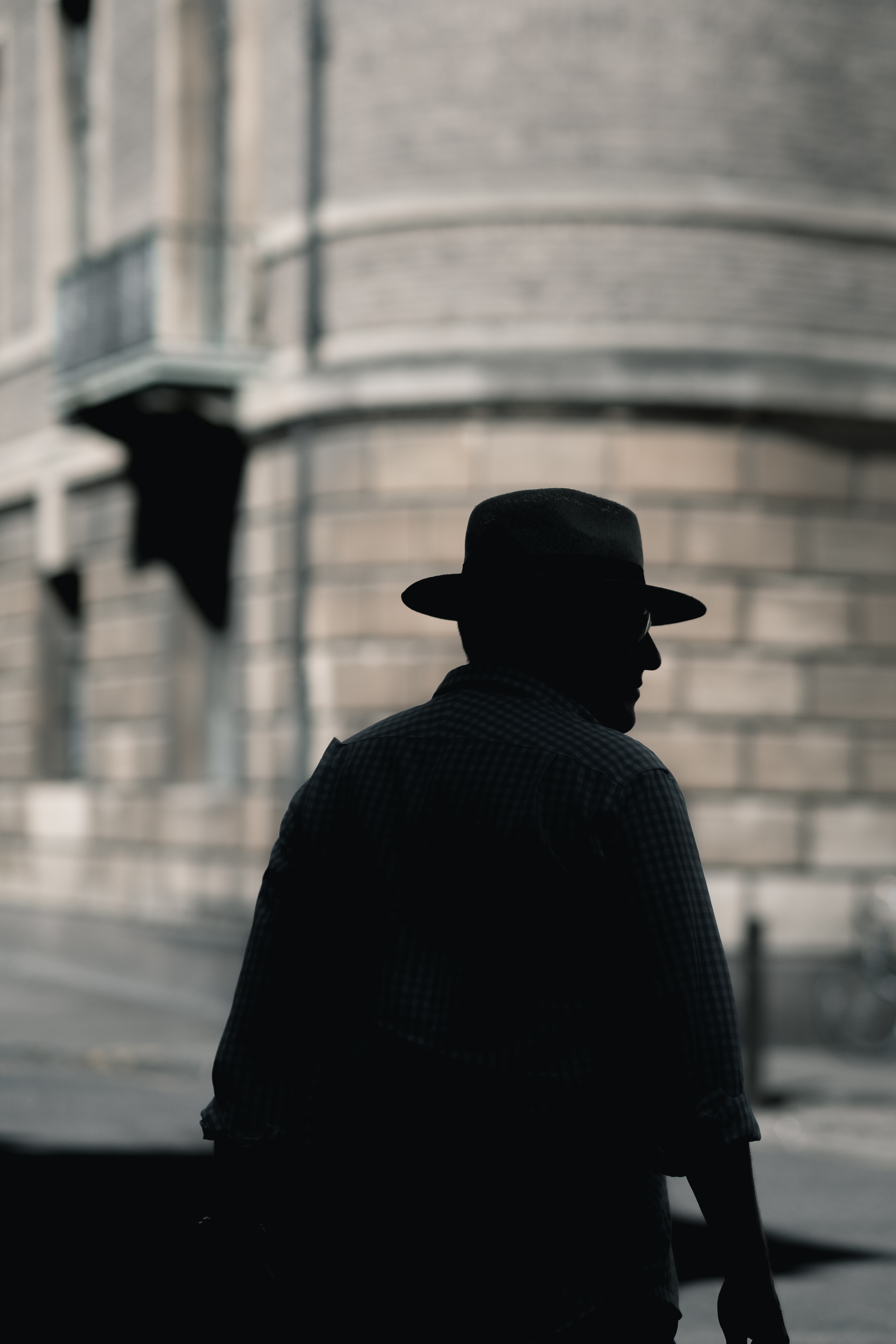 silhouette photo of a man with hat standing near concrete building at daytime