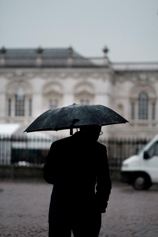 person holding black umbrella standing near white vehicle
