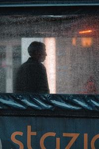 man standing near white concrete building