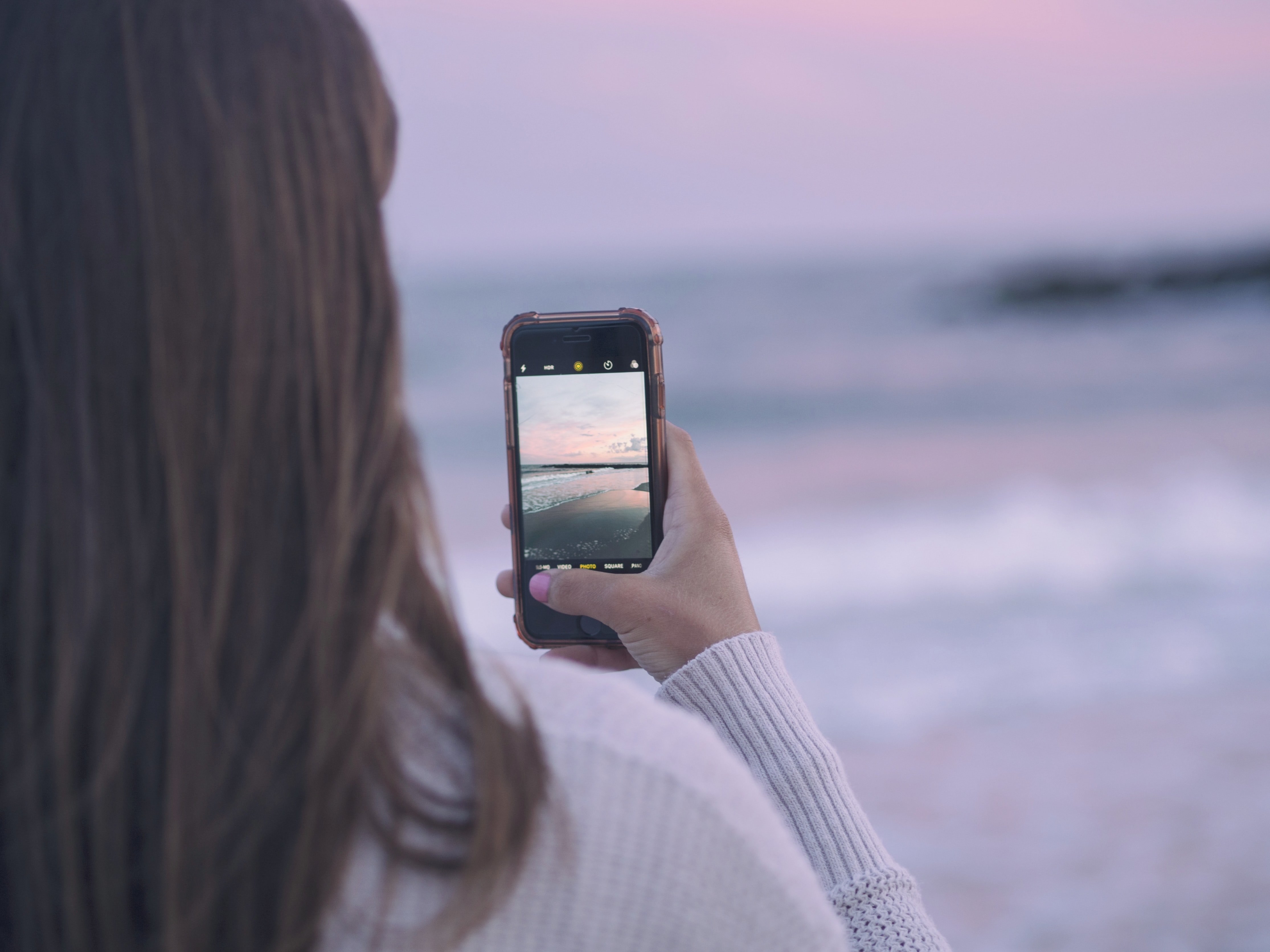 Woman taking a photo of the beach with a smartphone at Rockaway Beach
