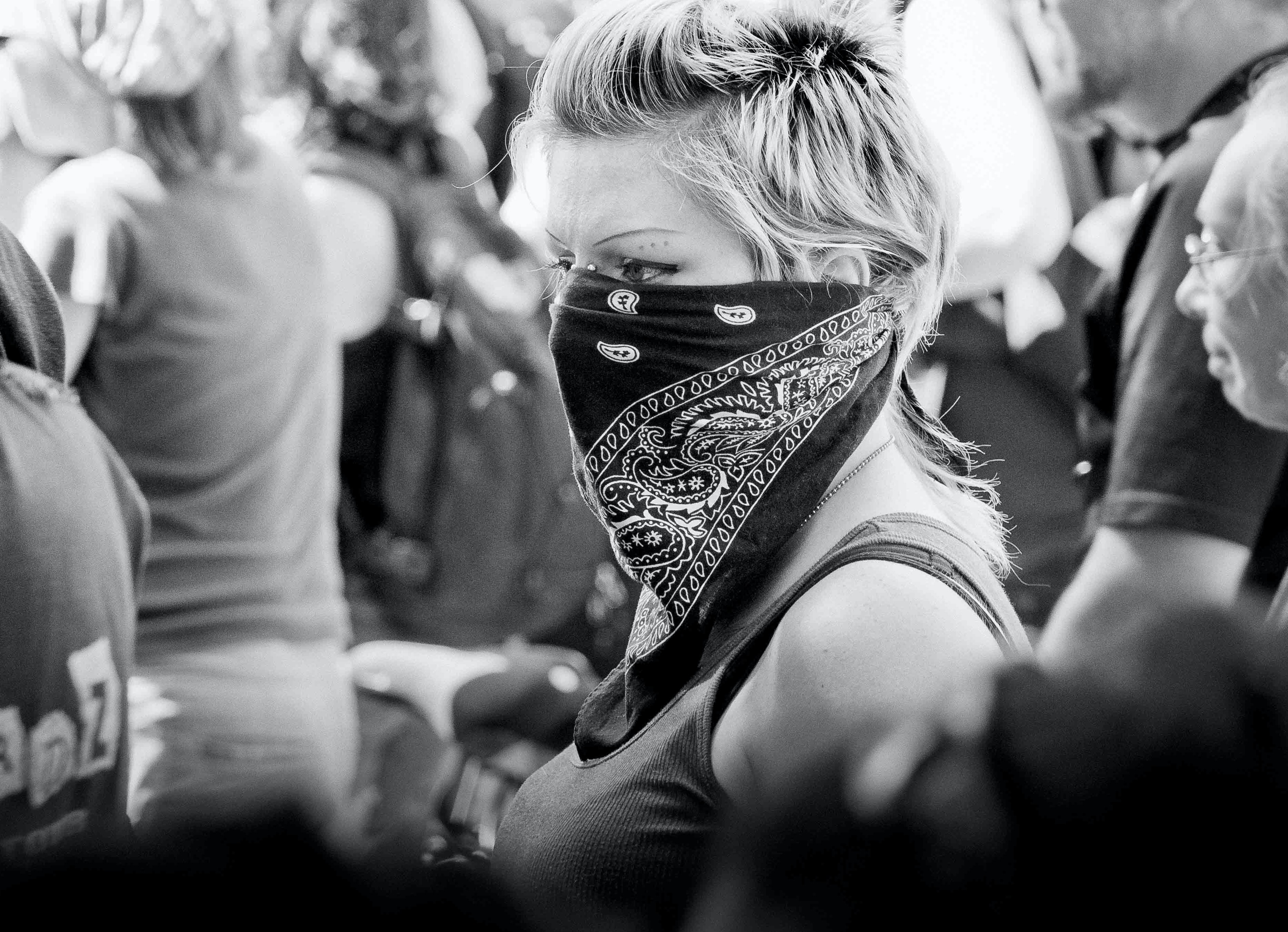 Black and white shot of young blonde haired woman in bandana with people, Toronto