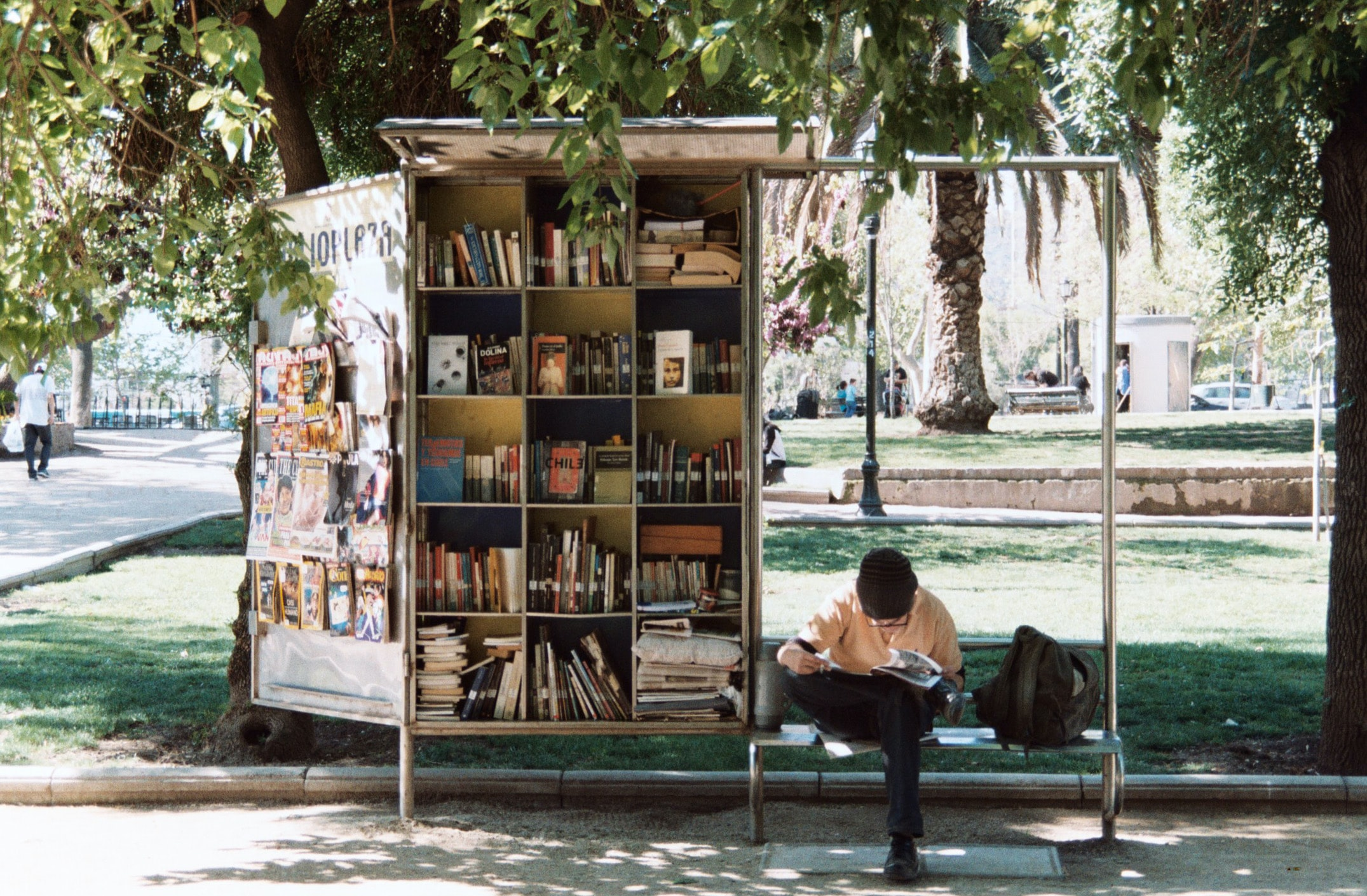 A man sitting on a bench next to a bookshelf in a park