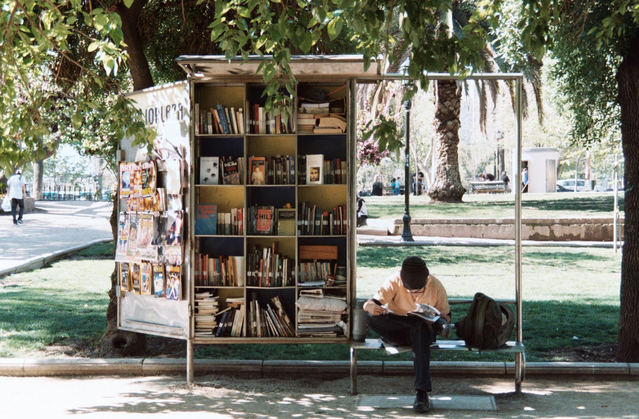 boy sitting on bench beside bookshelf