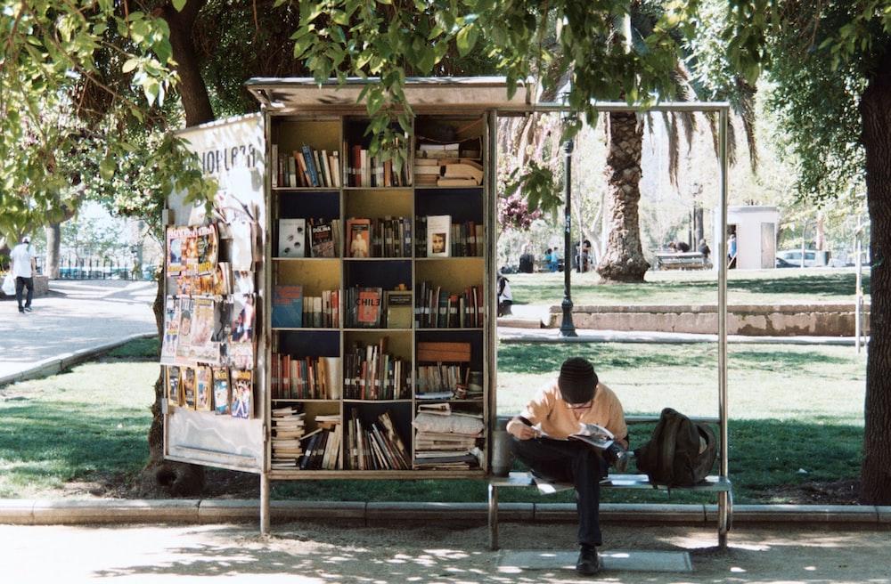 本棚の横にあるベンチに座っている少年