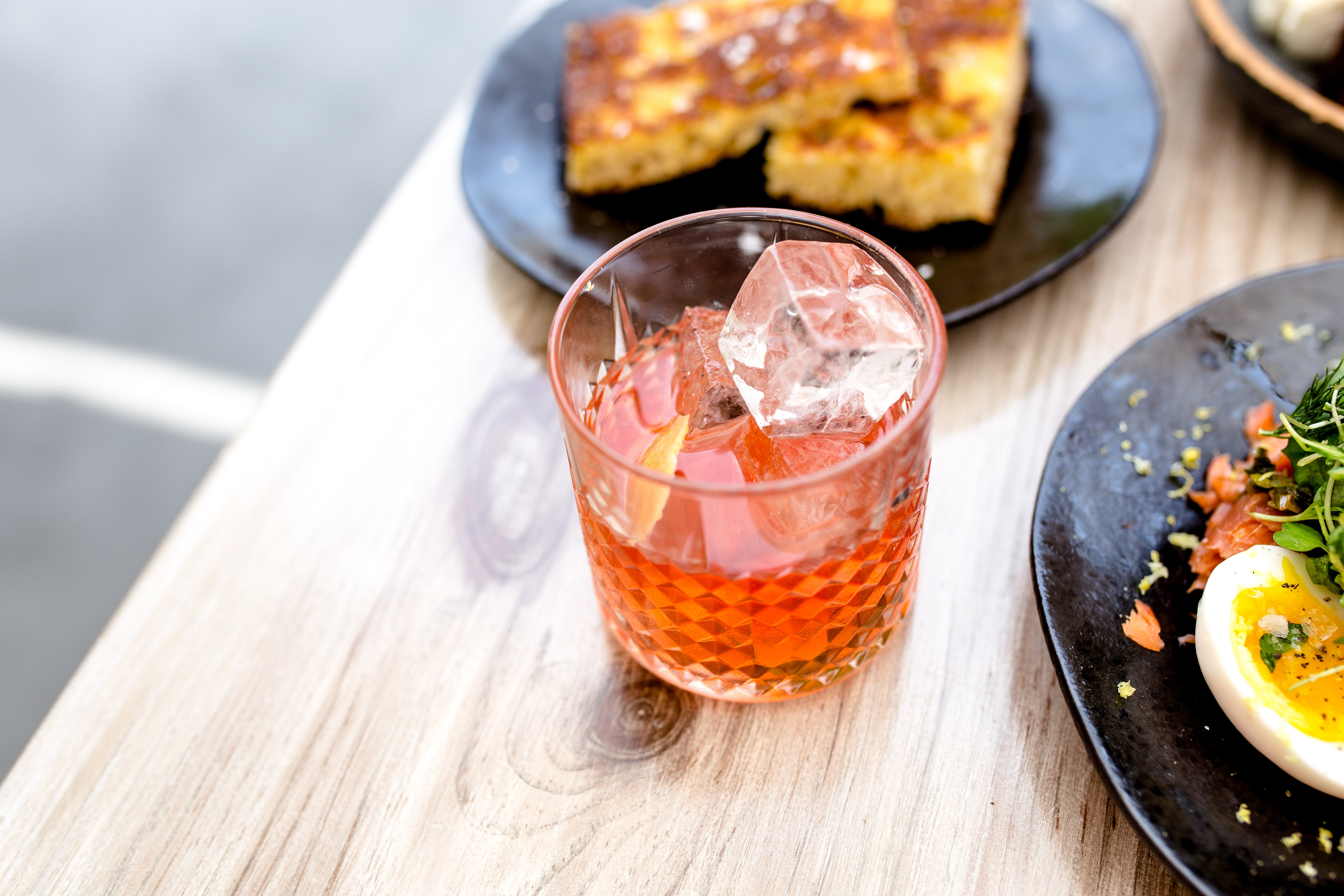 clear rocks glass with liquor and ice cubes beside black plate with breads on brown wooden table