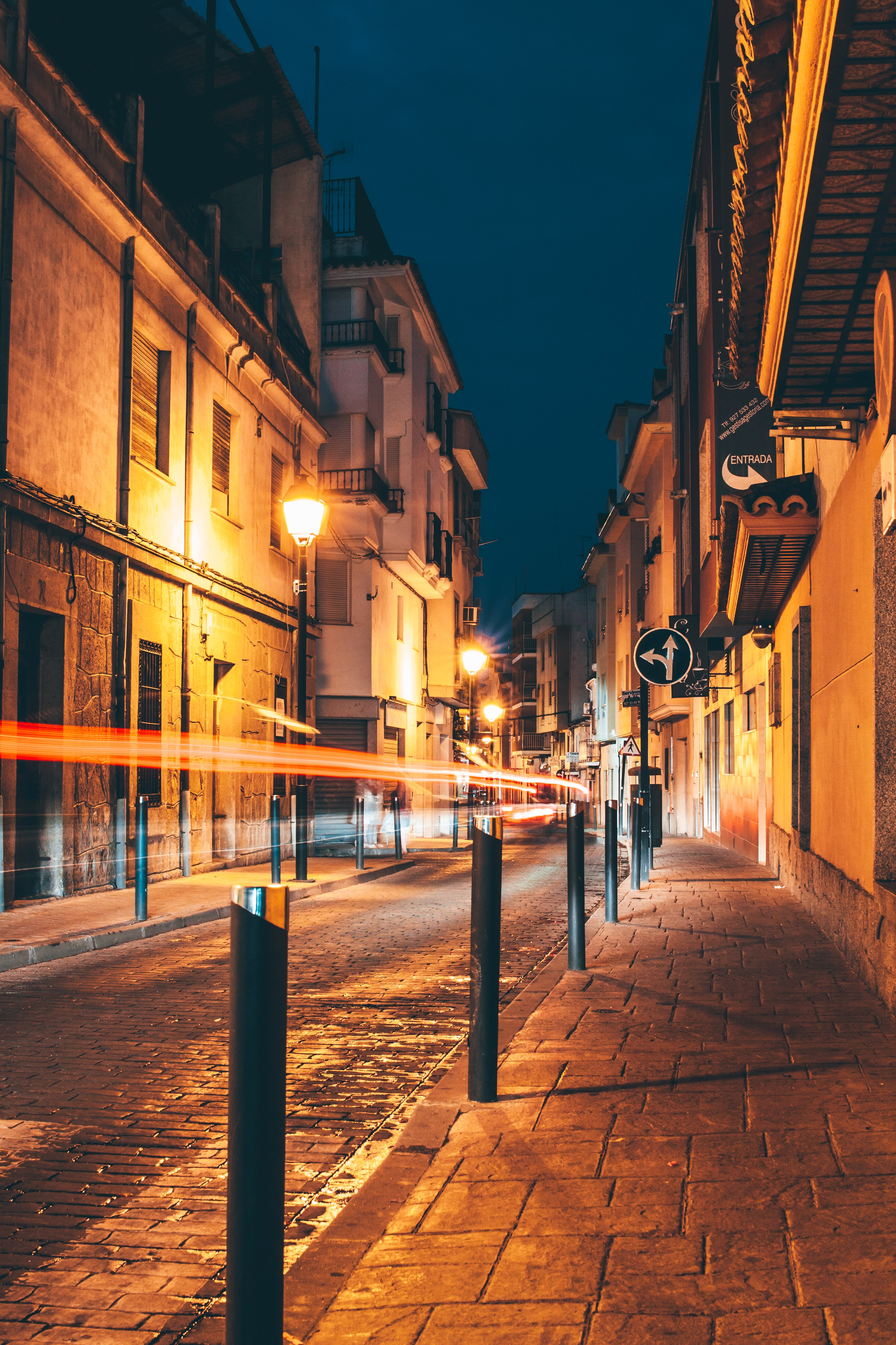 An early night shot of a street and the sidewalk in a historic part of town