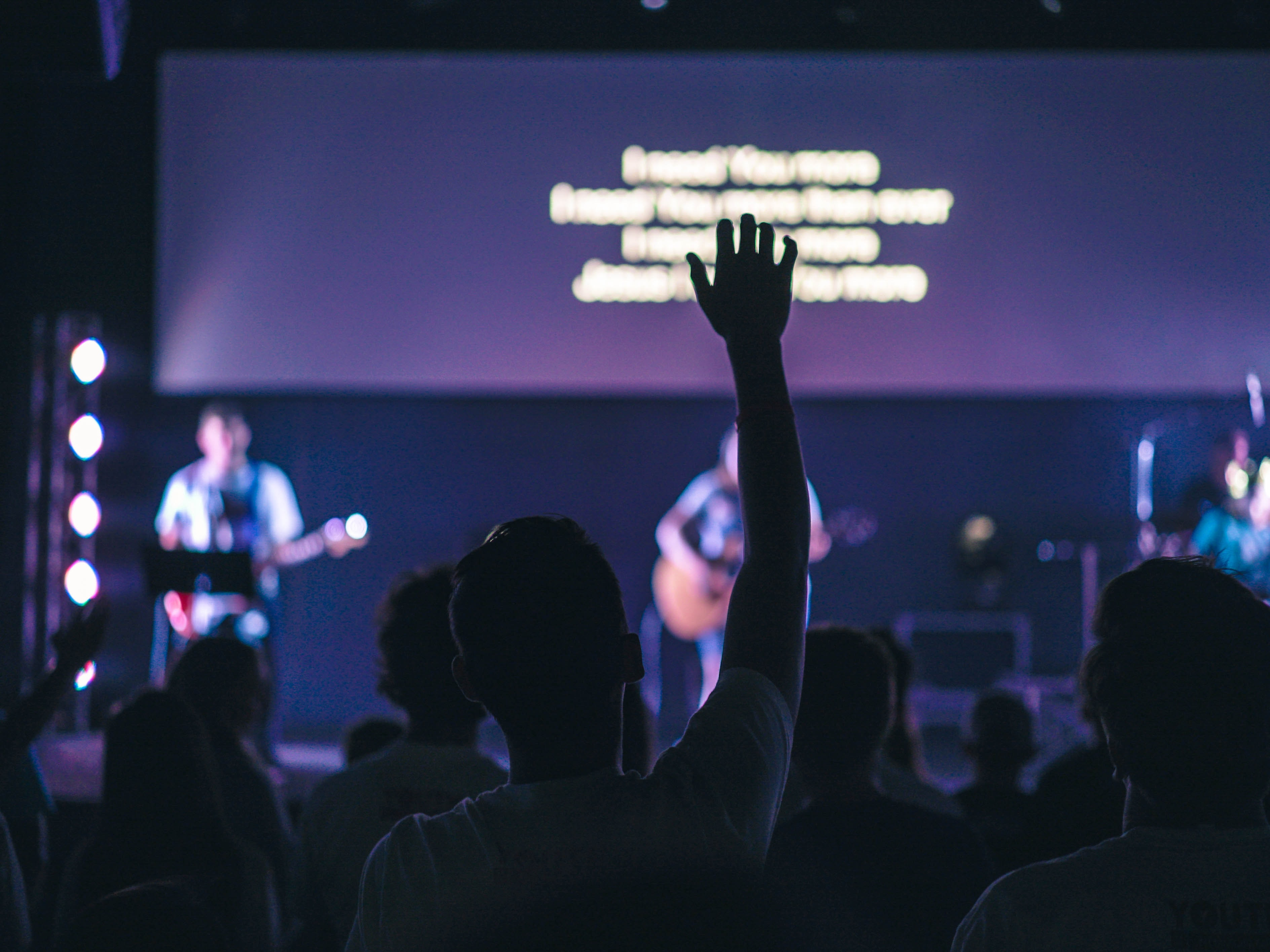 An audience member raises his hand during a music performance