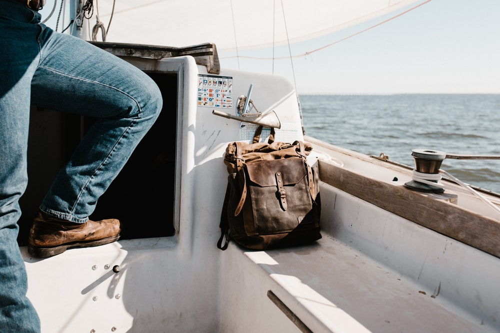 person in blue denim jeans on yacht beside brown bag