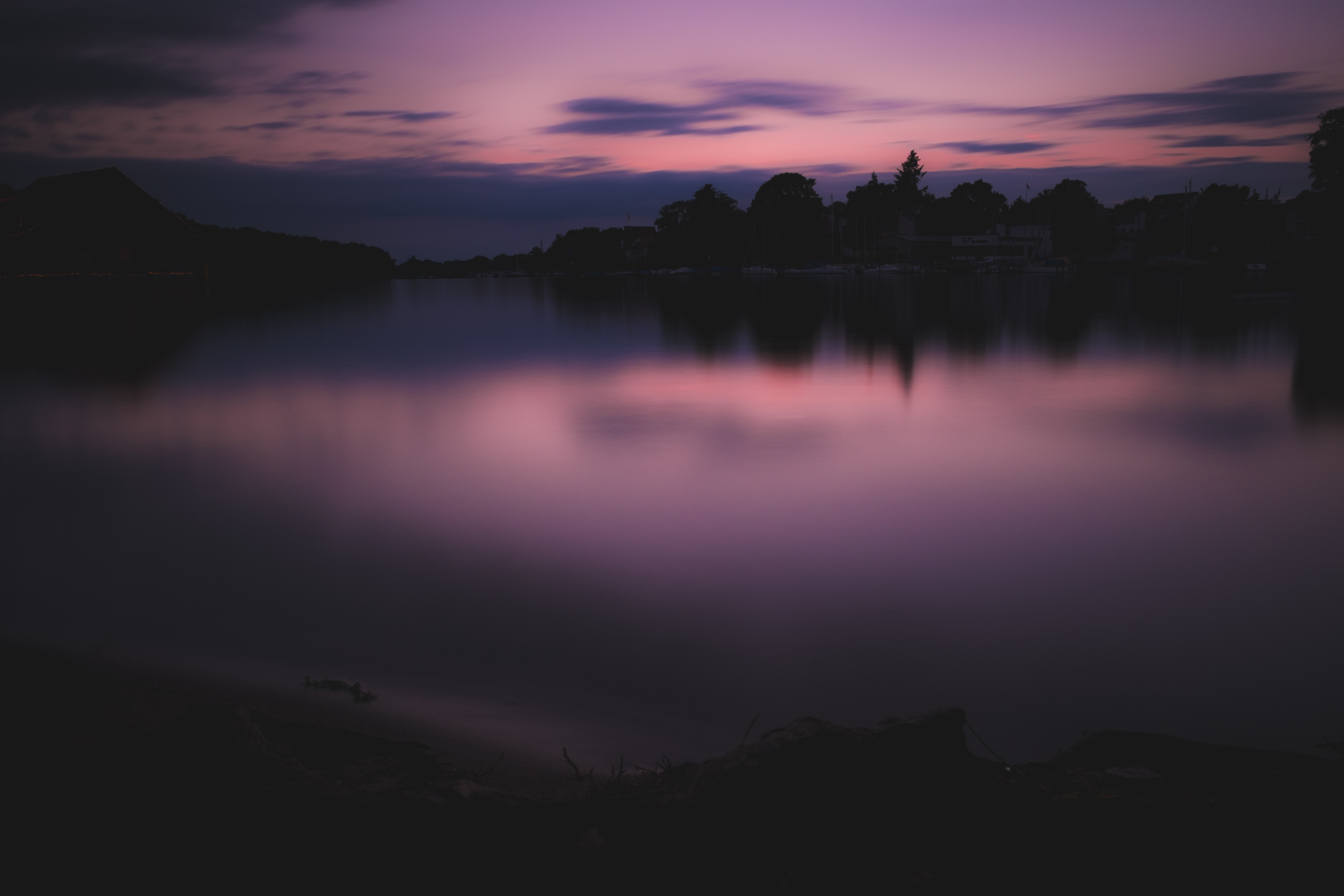 The sunset casting a purple reflection at twilight in the Müggelsee lake, Berlin, Germany