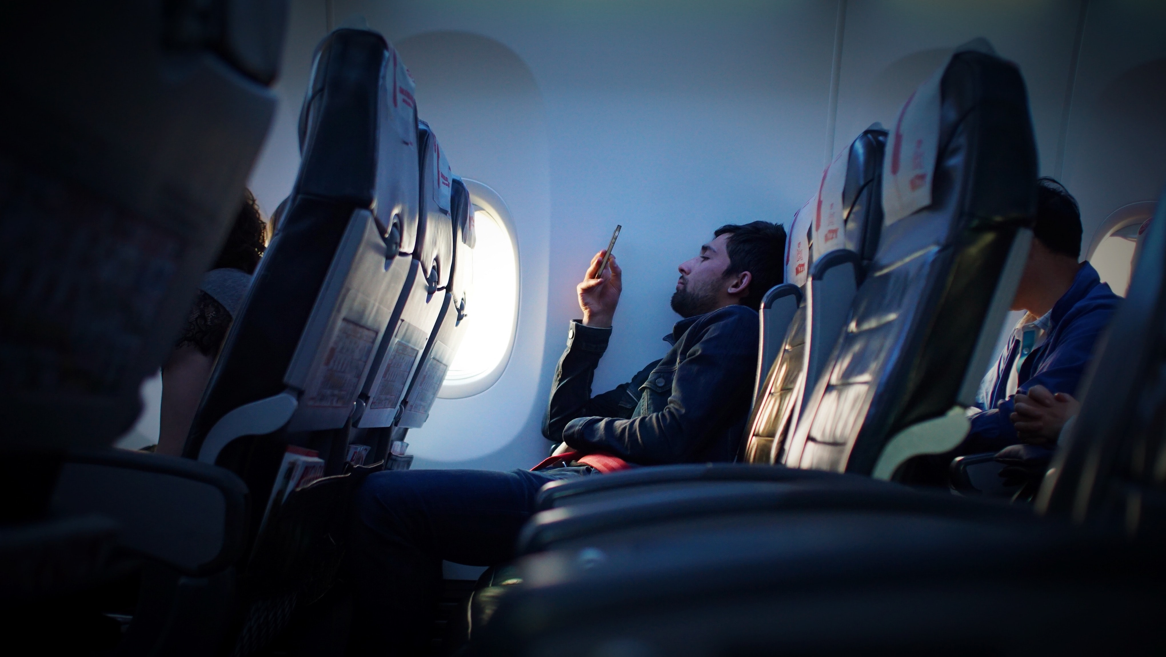 A bearded man using his phone on an airplane