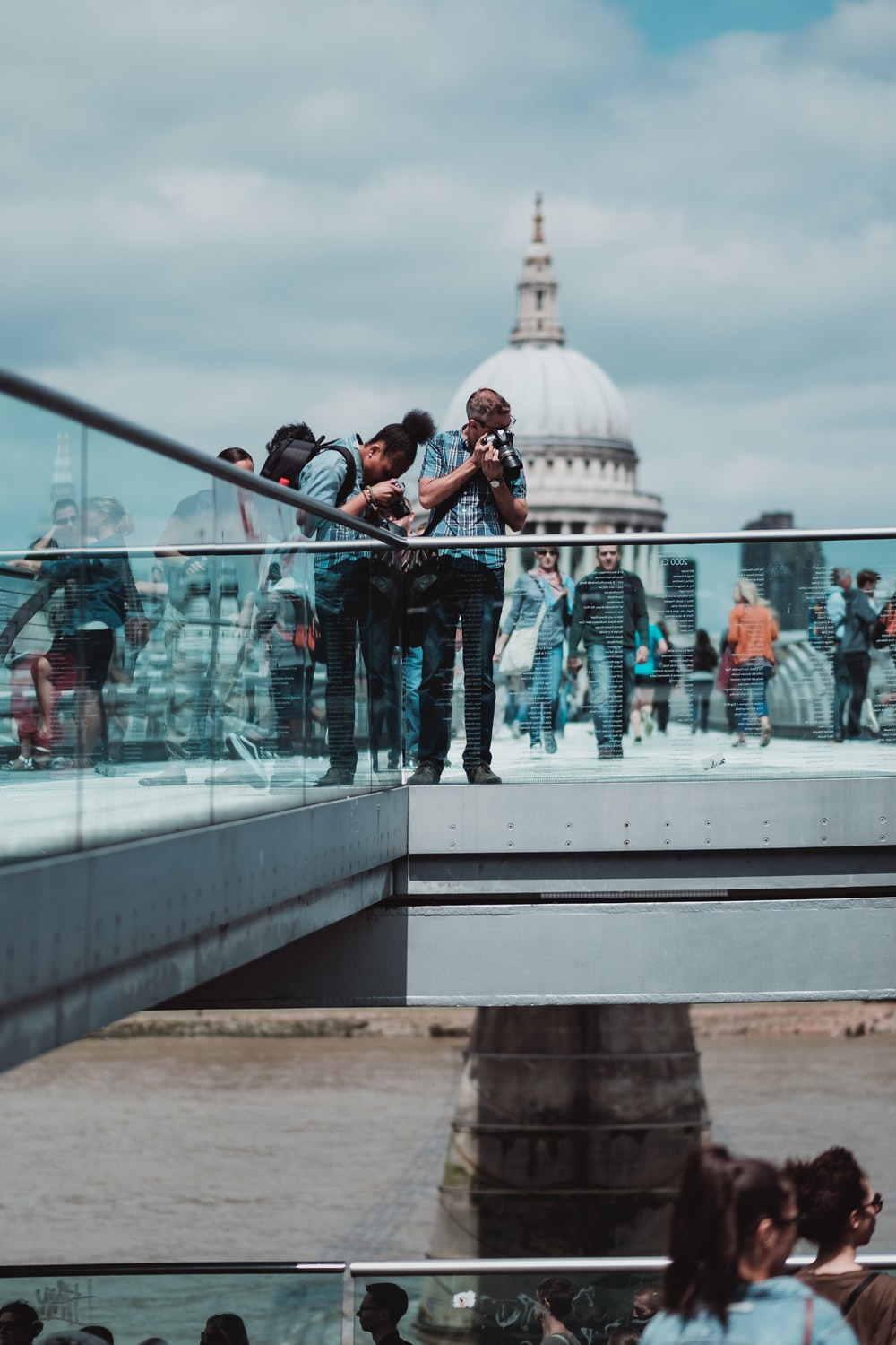 people standing over railings taking a photo