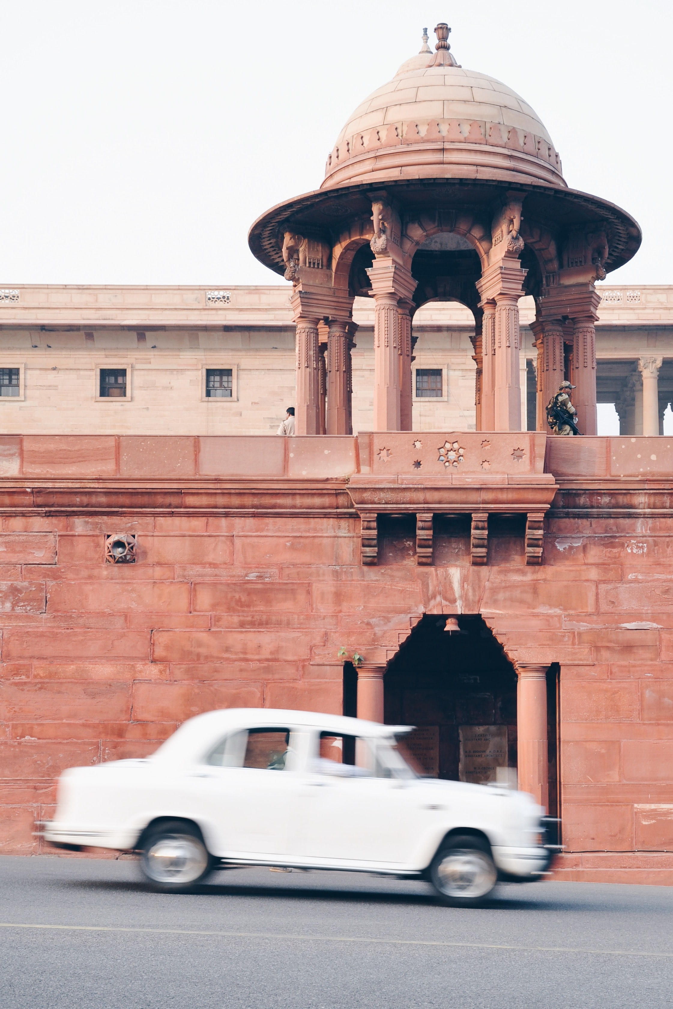White car driving past old stone wall in Delhi