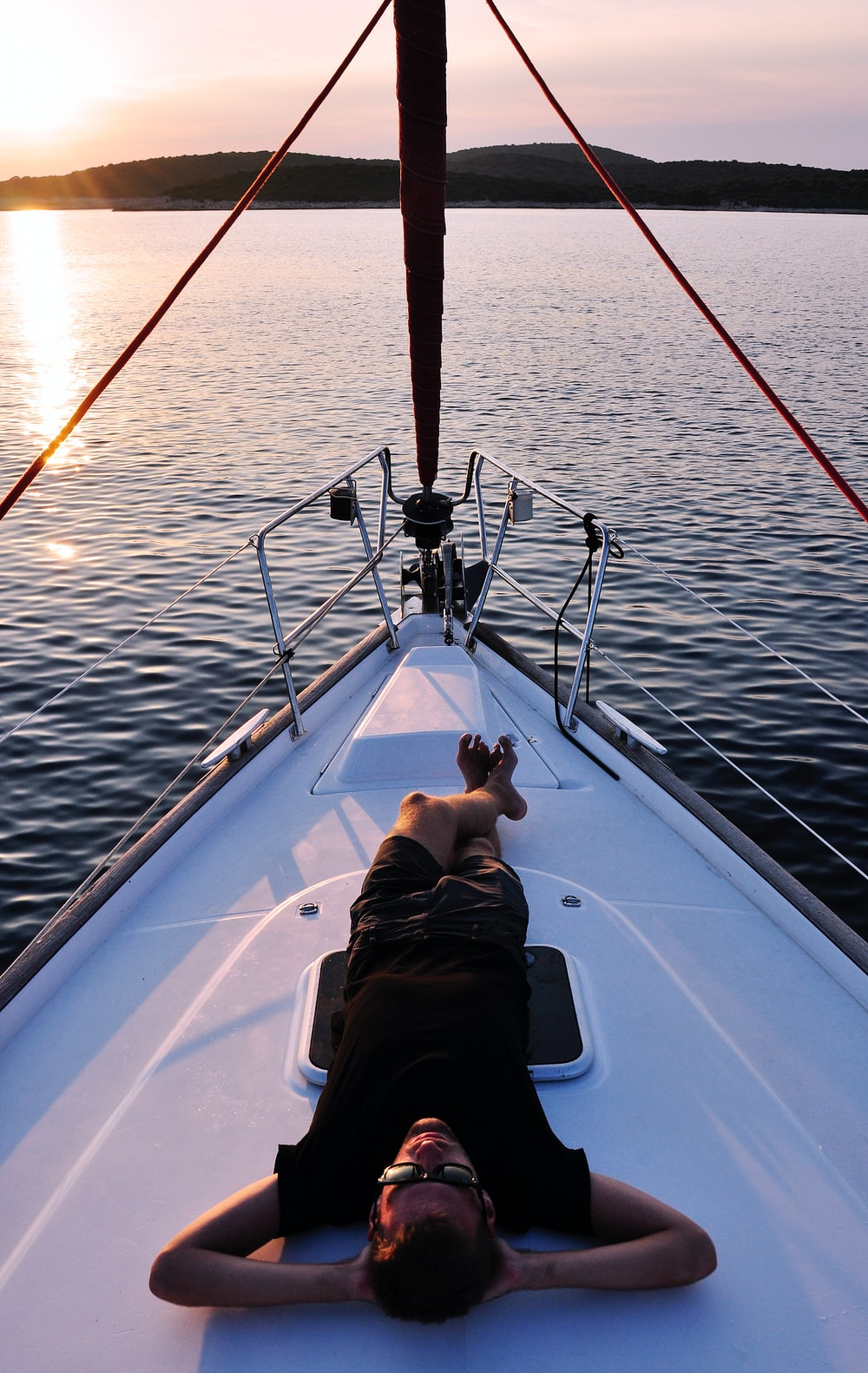 A man relaxing on his yacht on the calm water at Palinski Island at sunset