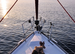 man lying on white boat