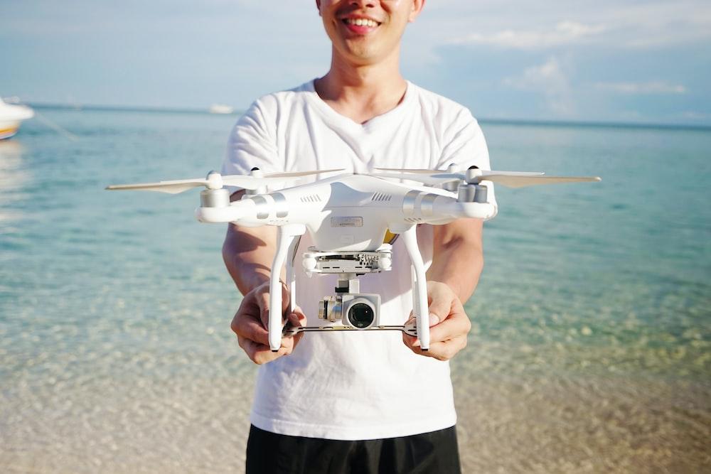 man holding DJI Phatom Professional on beach