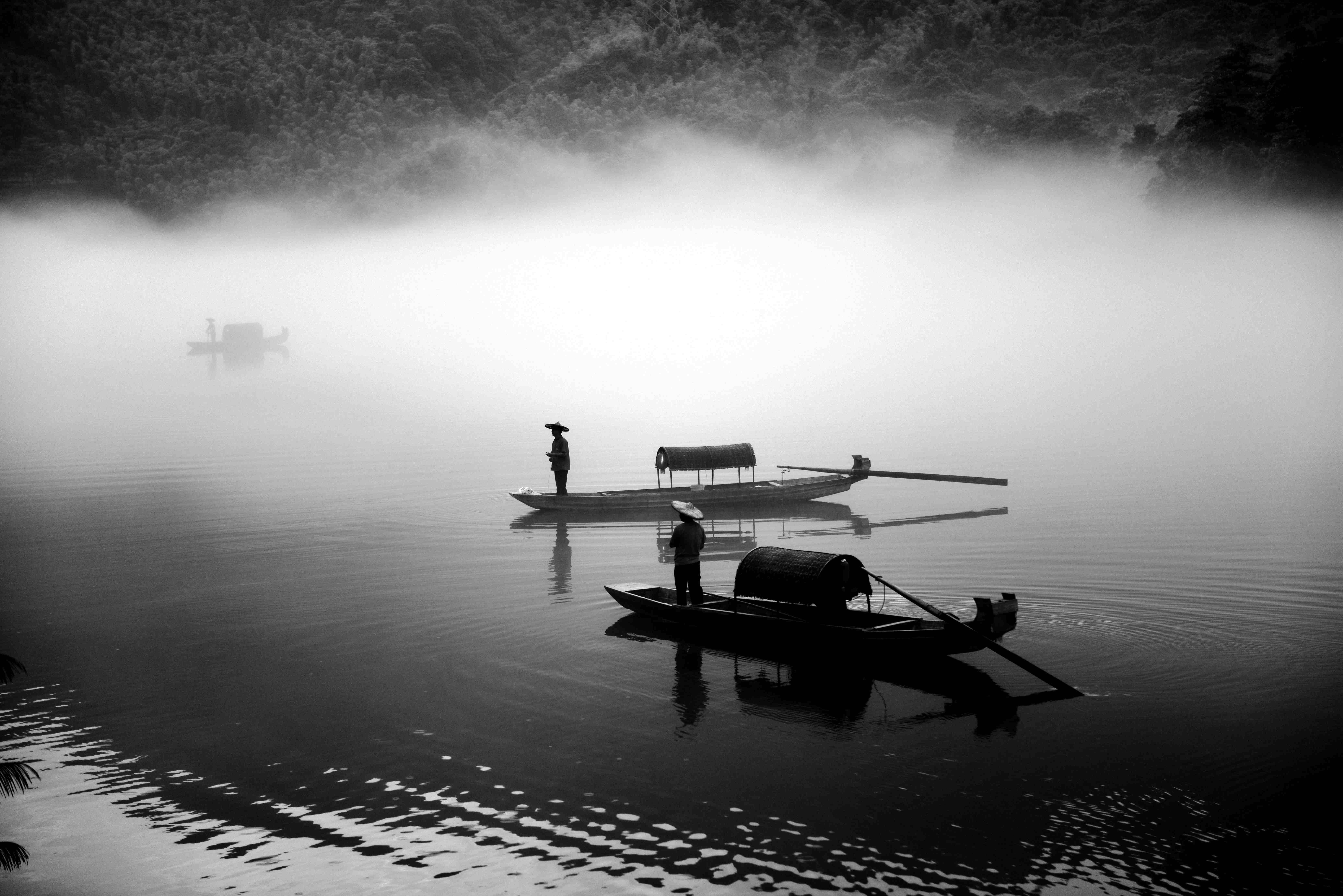 Silhouettes of fishermen on boats in misty waters