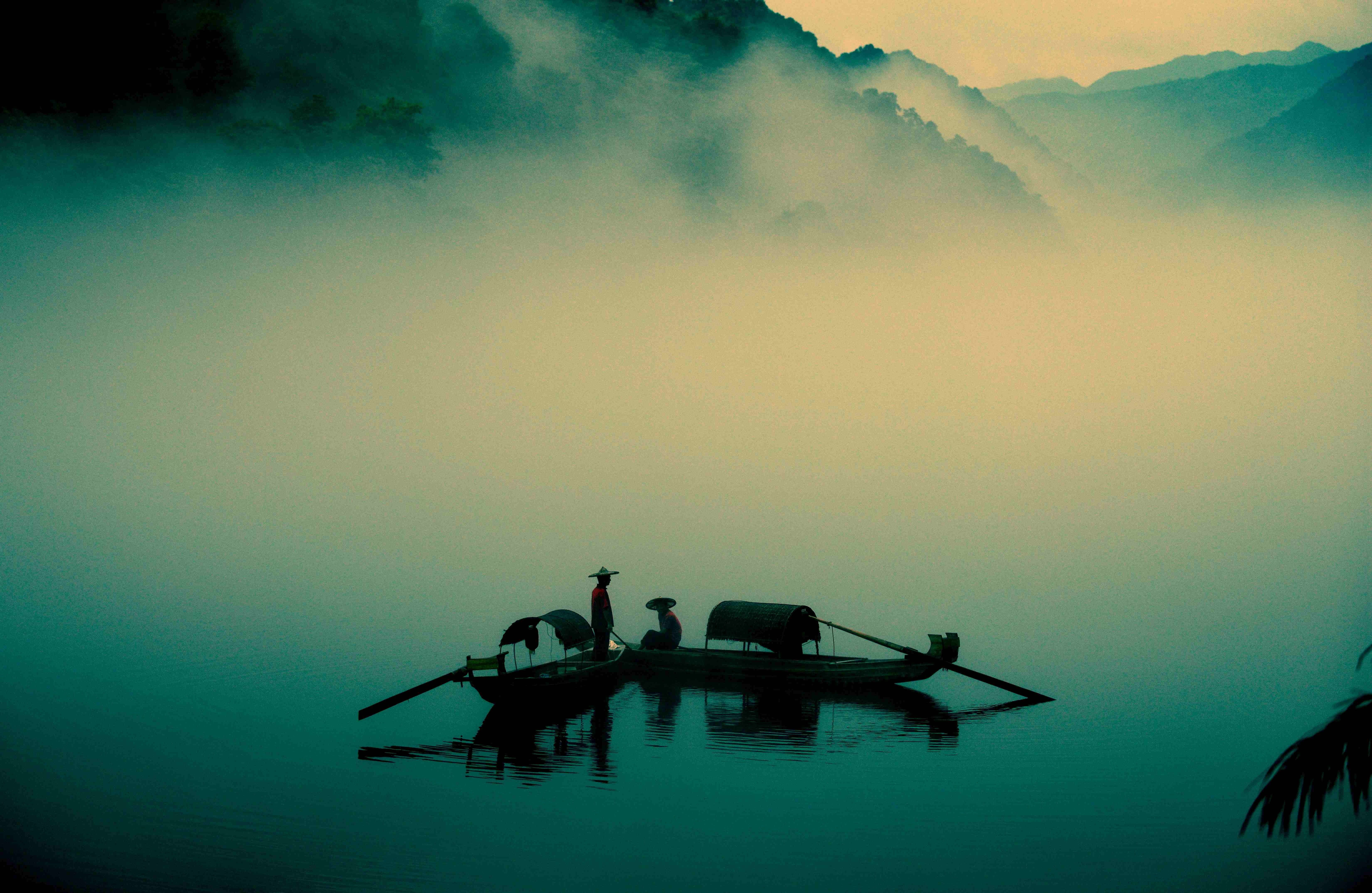 Two fisherman wearing hats on their canoes on a lake in the morning fog