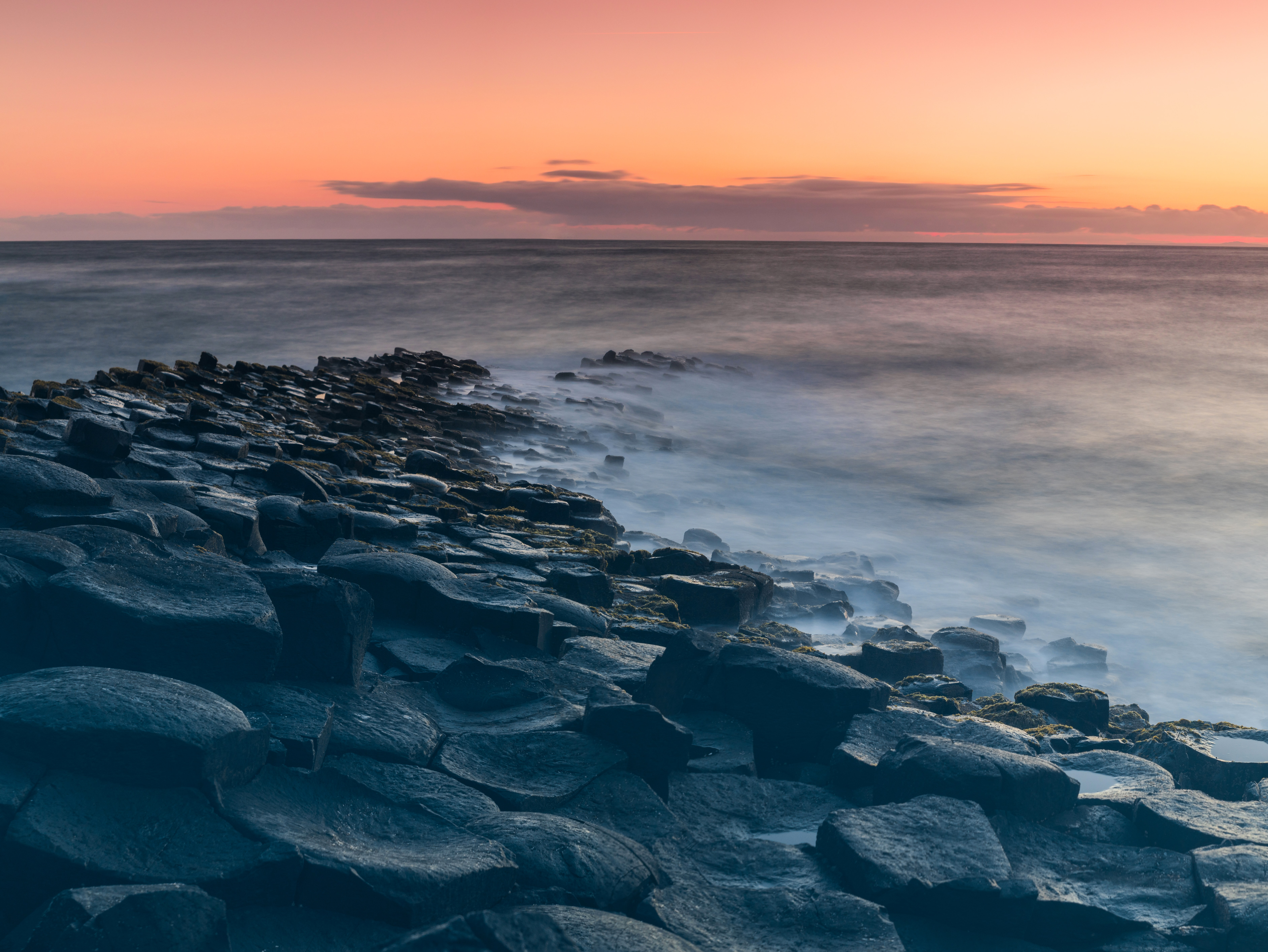 The Giant's causeway with a misty sea breaking on the rocks and a pink sky illuminating the horizon during dawn-or-dusk