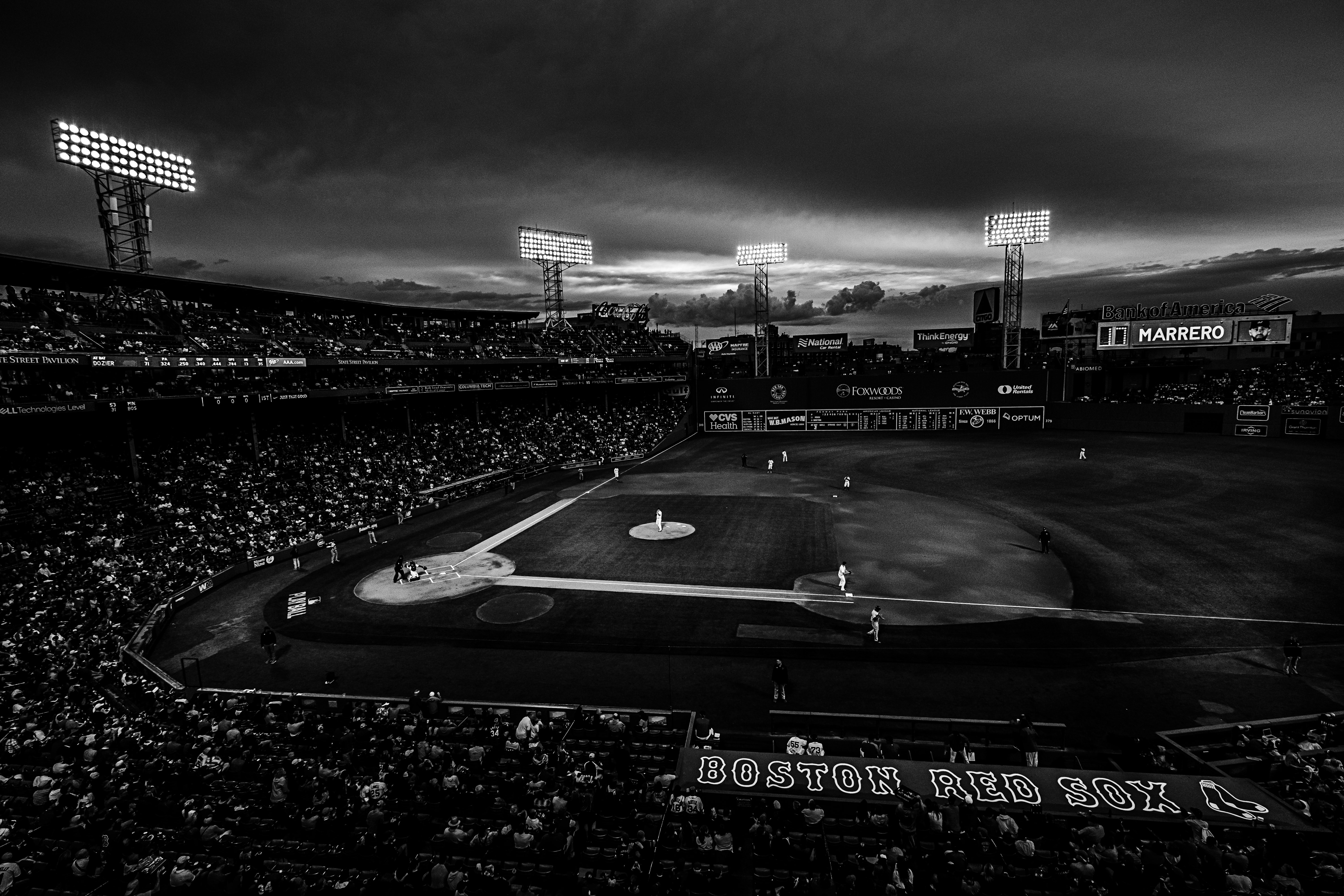 A black and white shot at night from behind the crowd at a Boston Red Sox game