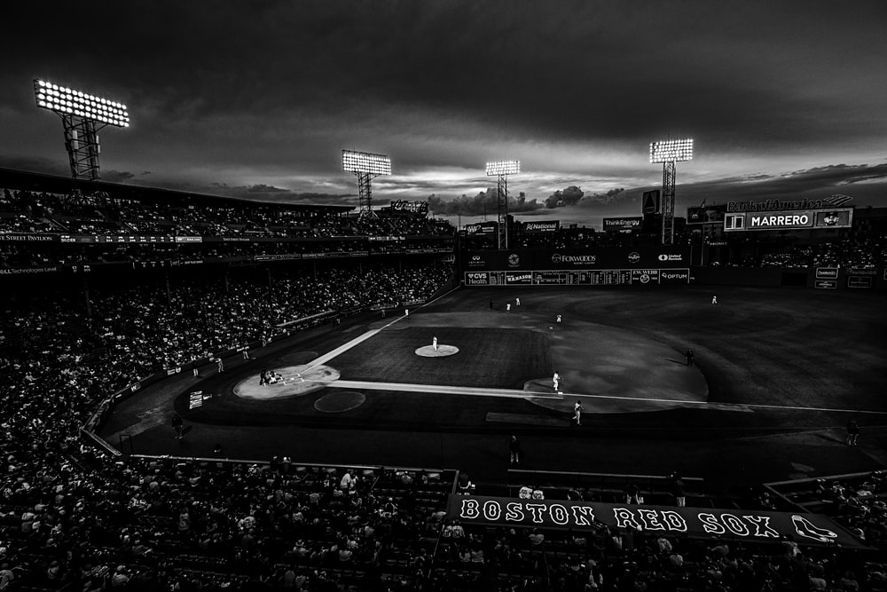 grayscale photography of baseball field with people on bleachers