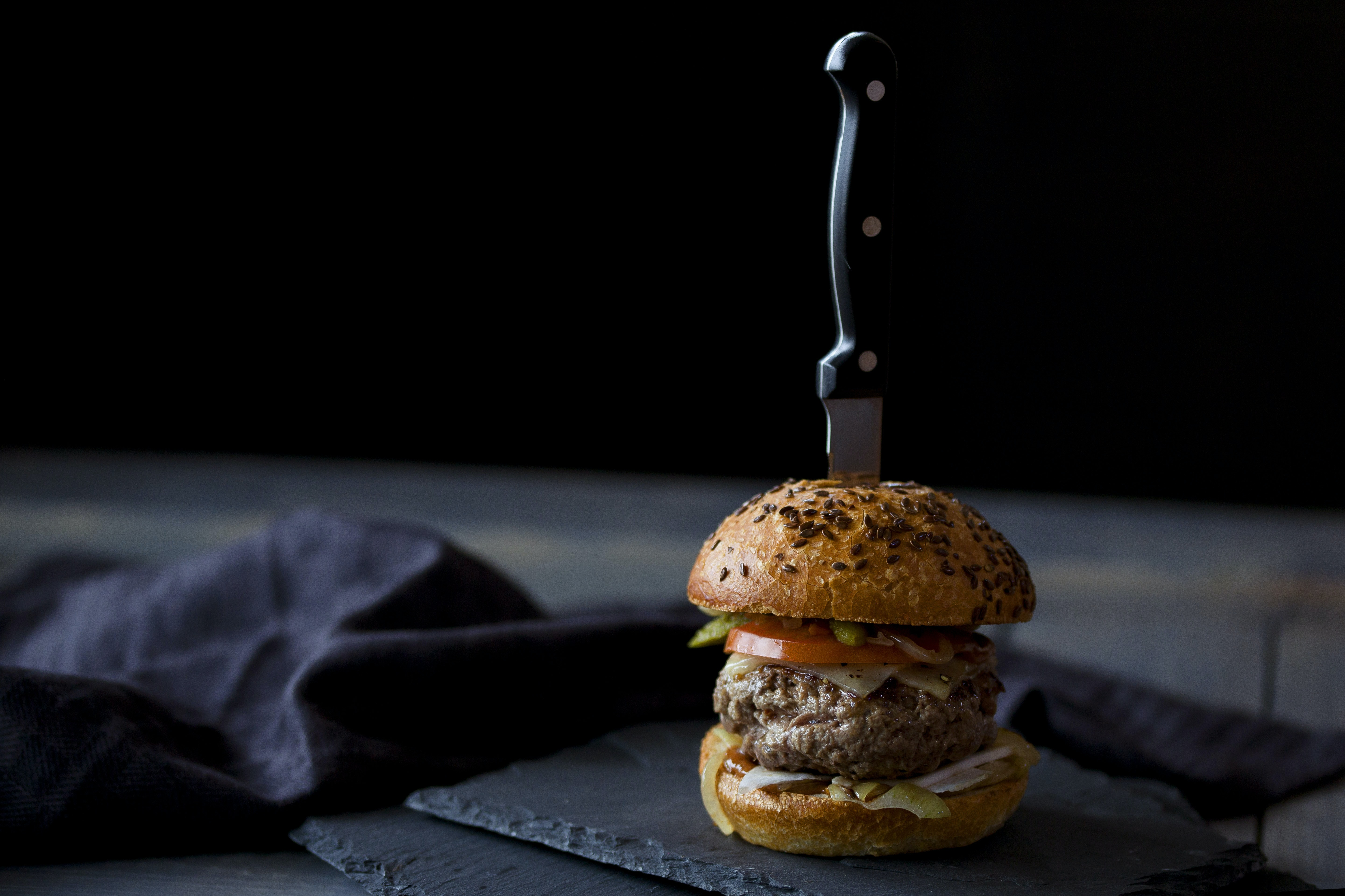 burger skewered with knife near black textile