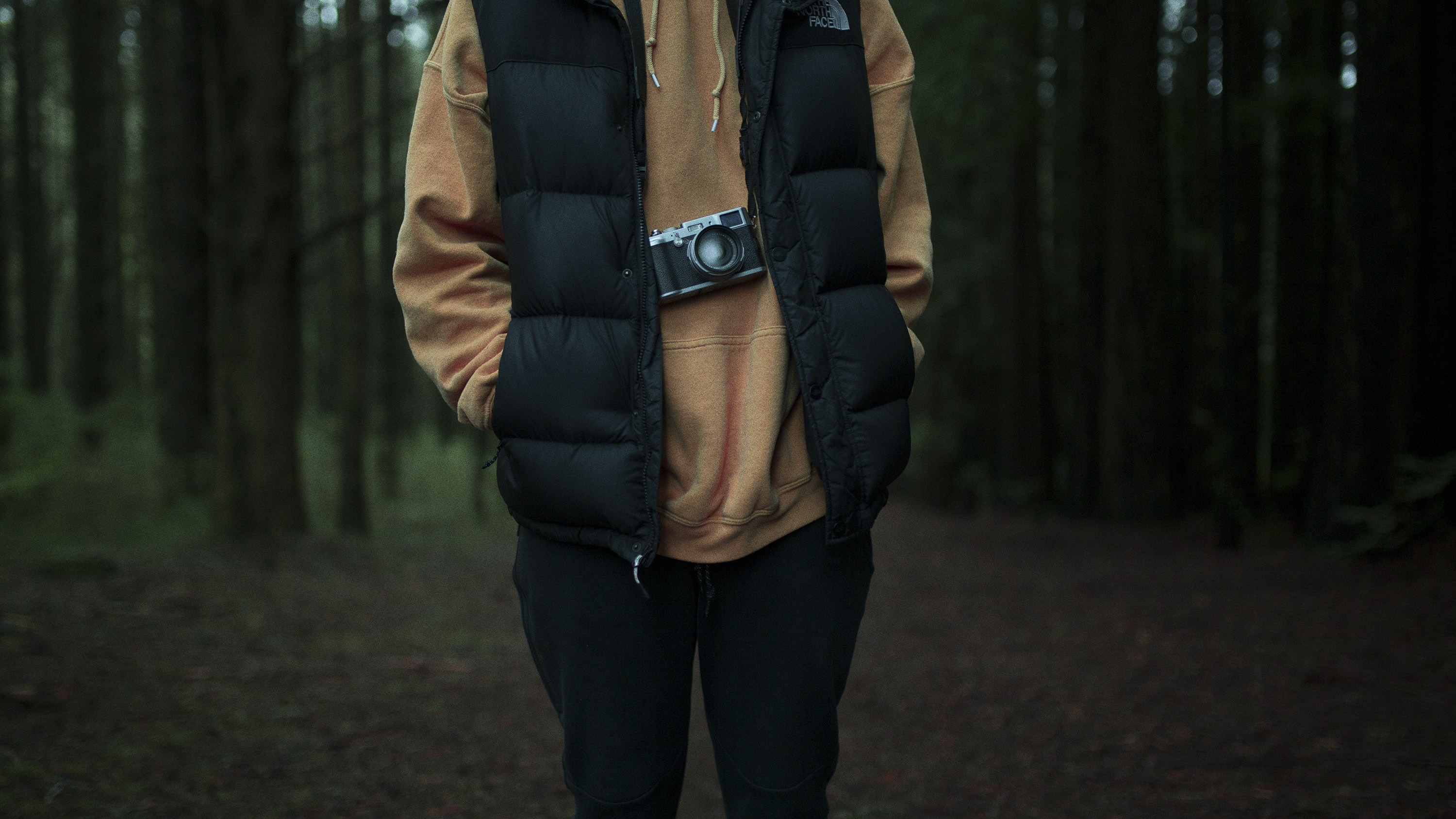Close-up of a person with a camera hanging from their neck in a forest
