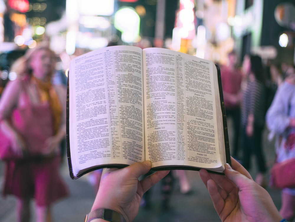 person holding bible on road with people walking on sidewalk beside buildings during nighttime