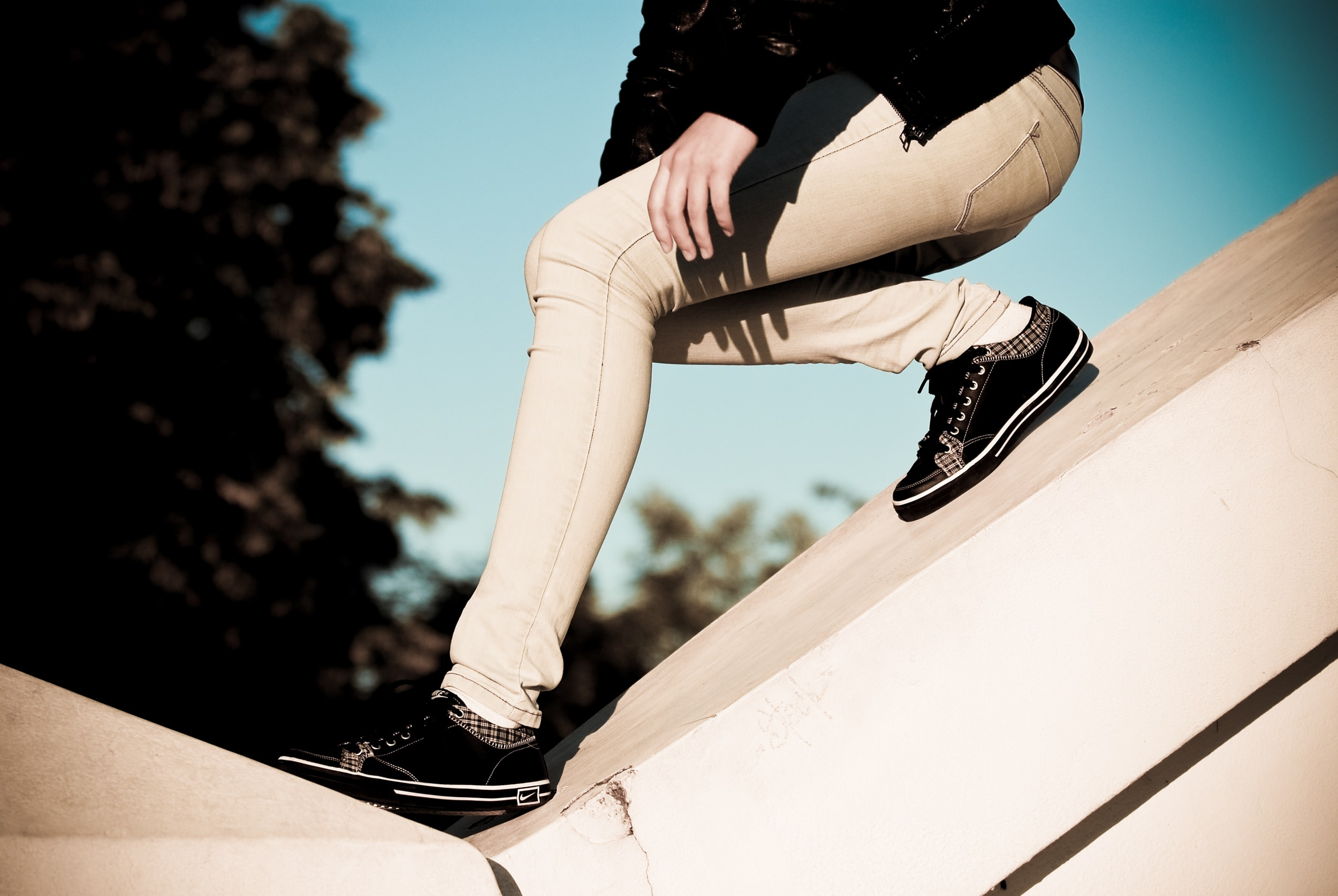 person wearing beige pants sliding on slope