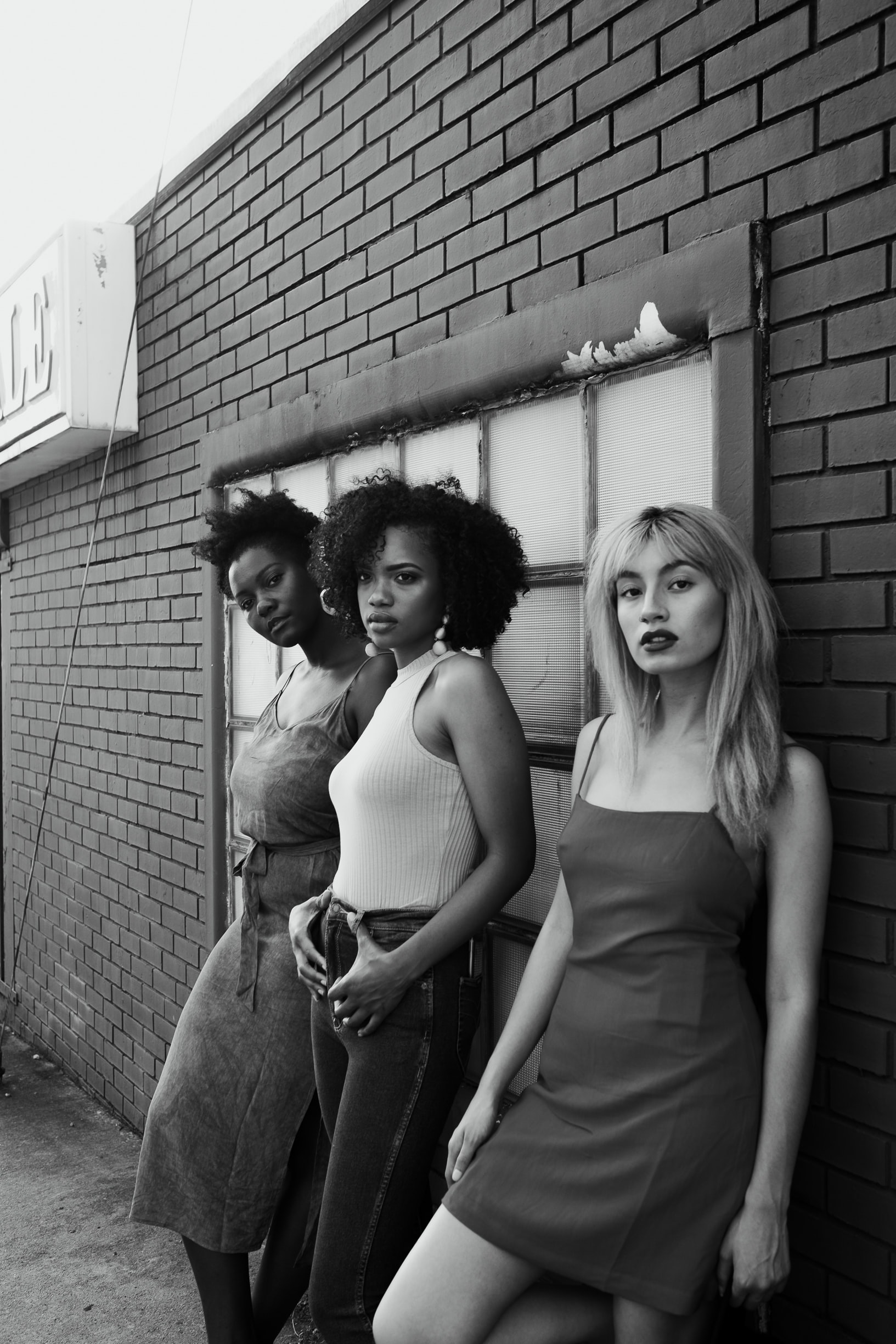 grayscale photo of three women leaning on wall