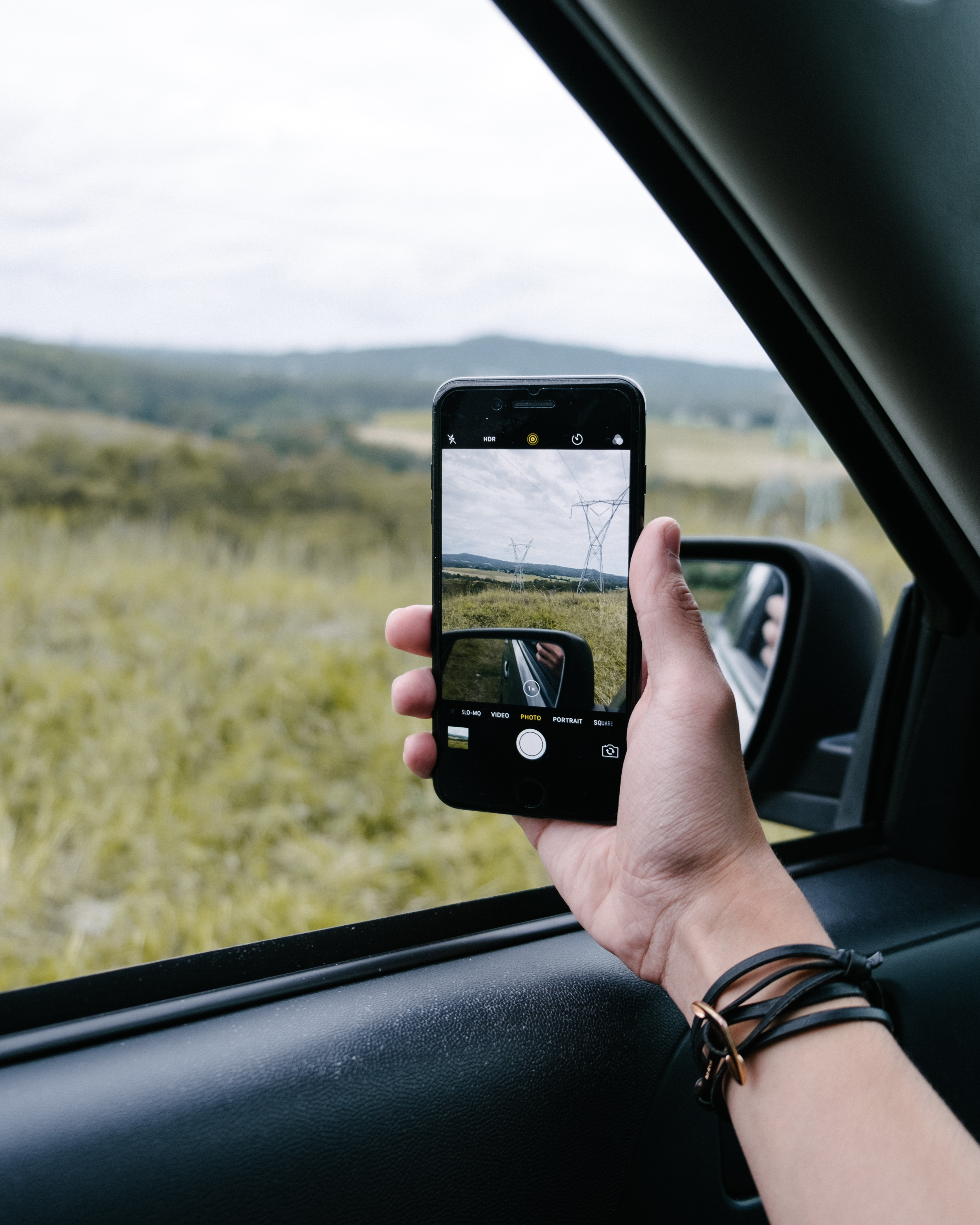 A person taking a picture out their car window with their smartphone.