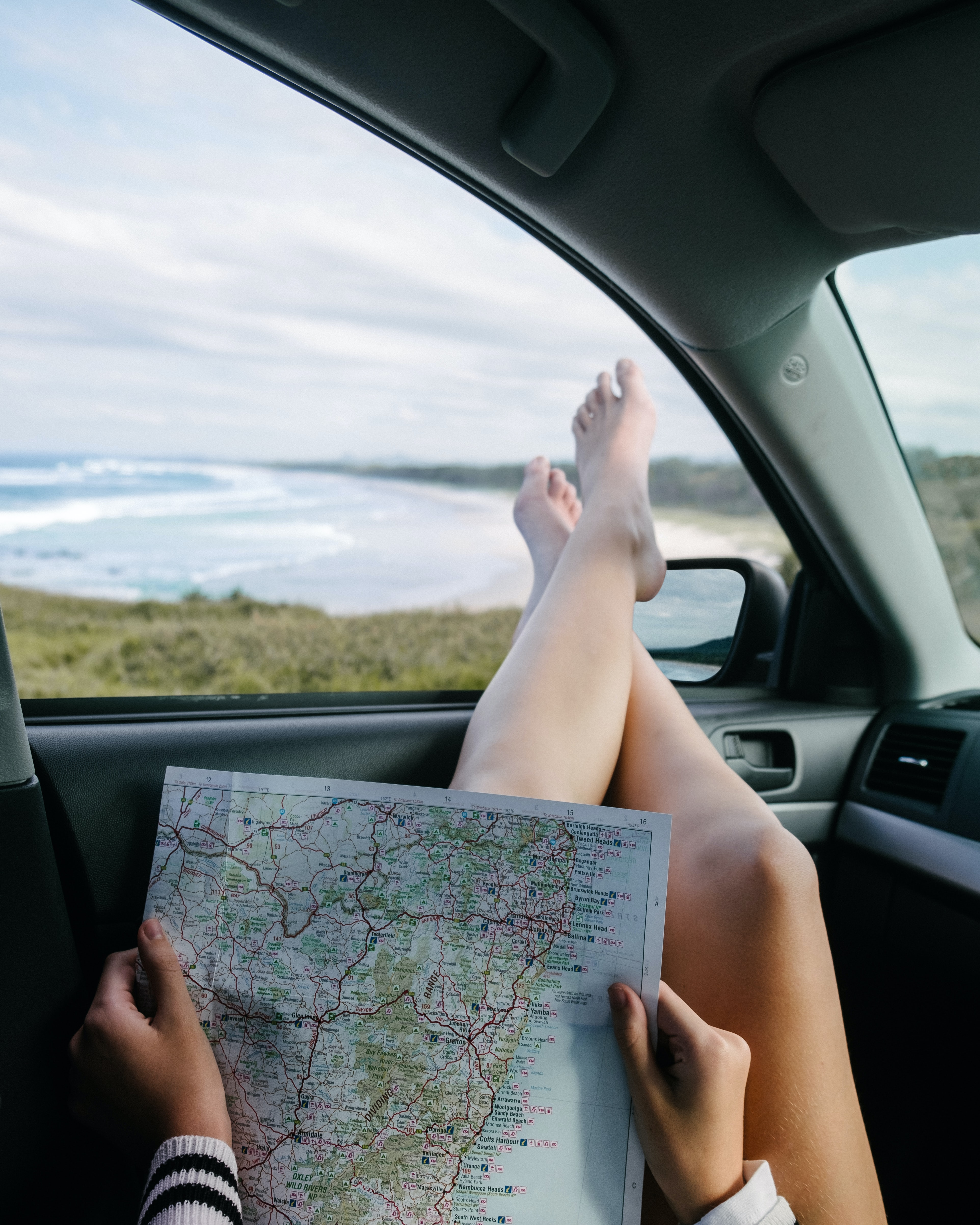 A woman reads a map with Gold Coast beach in the background.