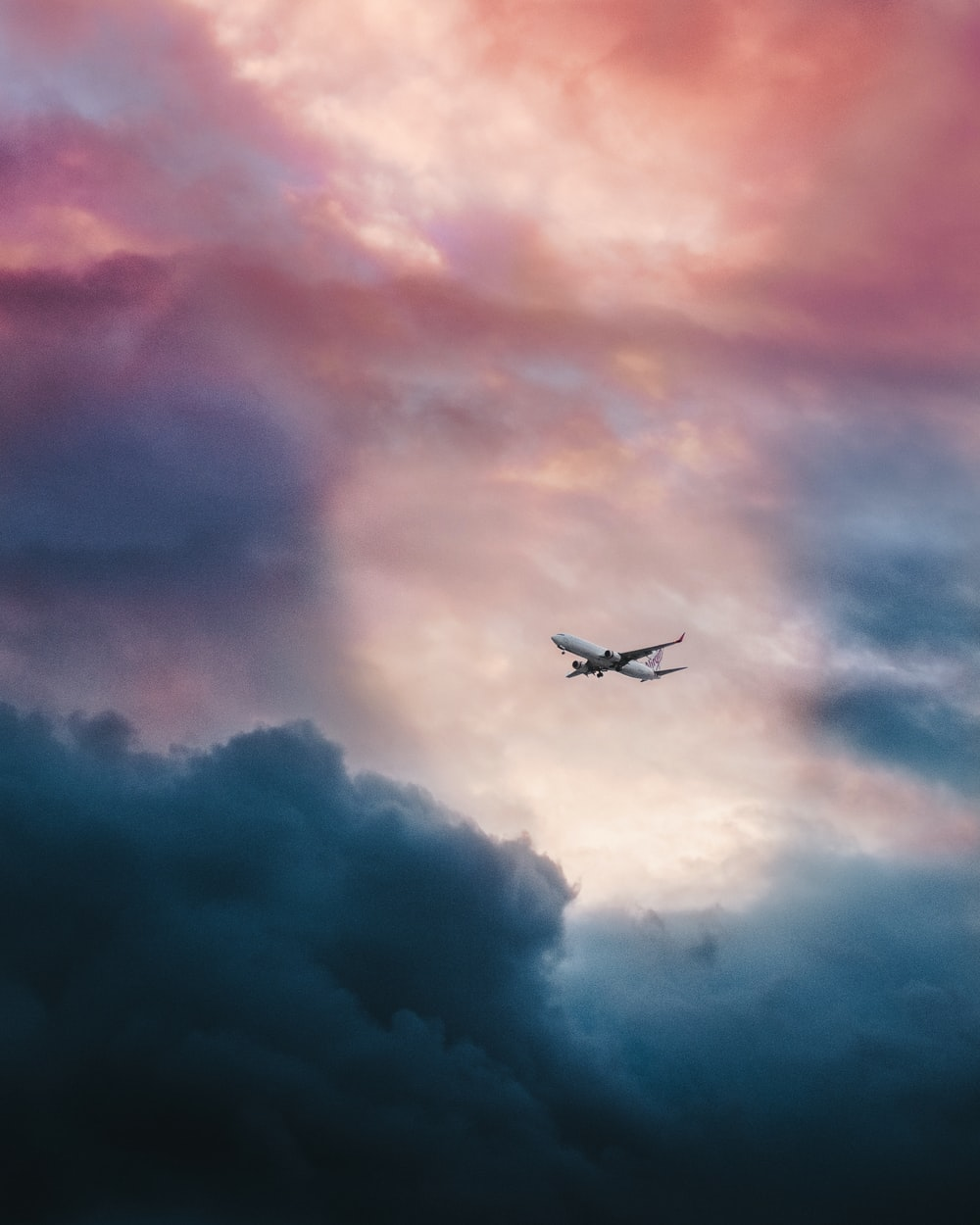 white plane flying over gray clouds