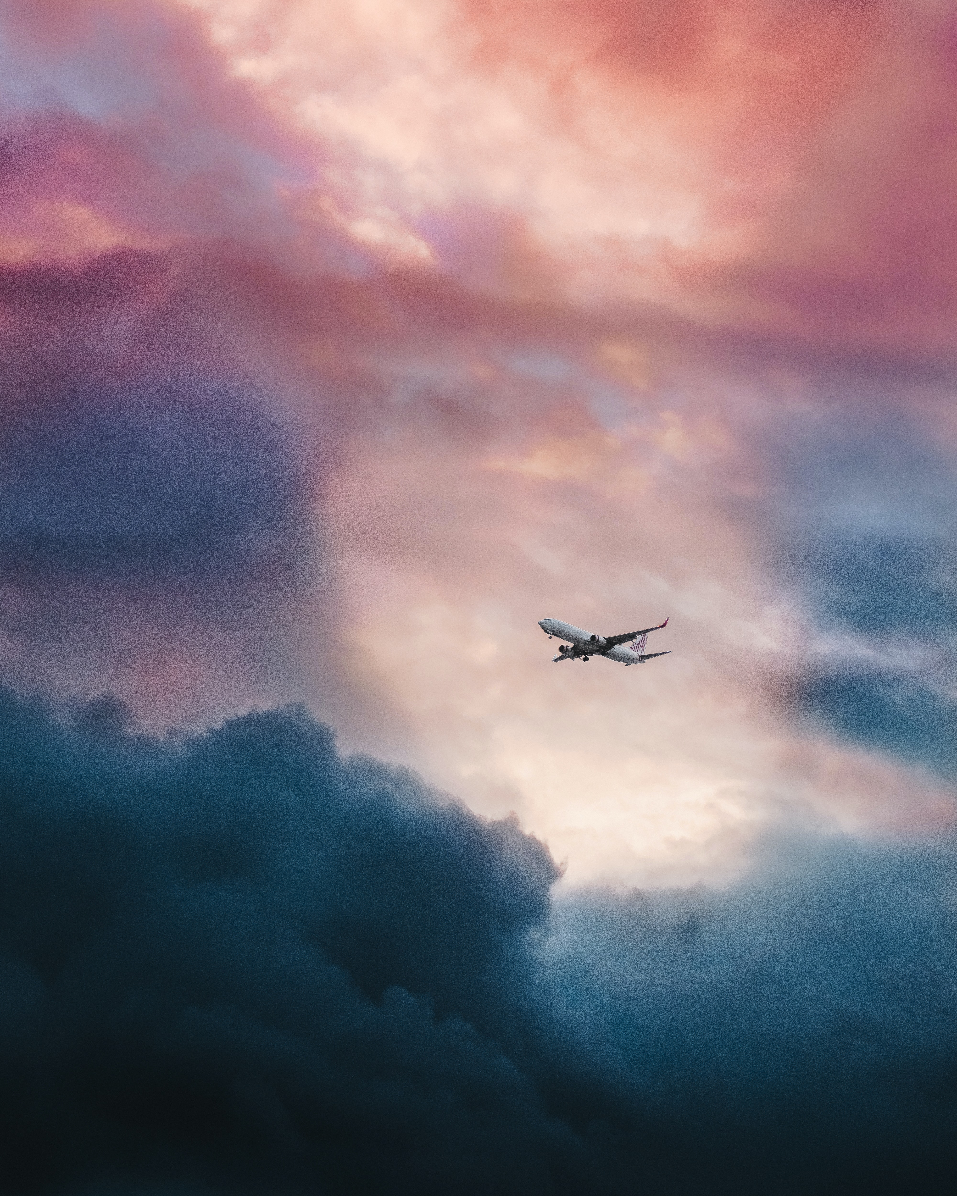 A low-angle shot of an airplane in flight with sun shining through the clouds