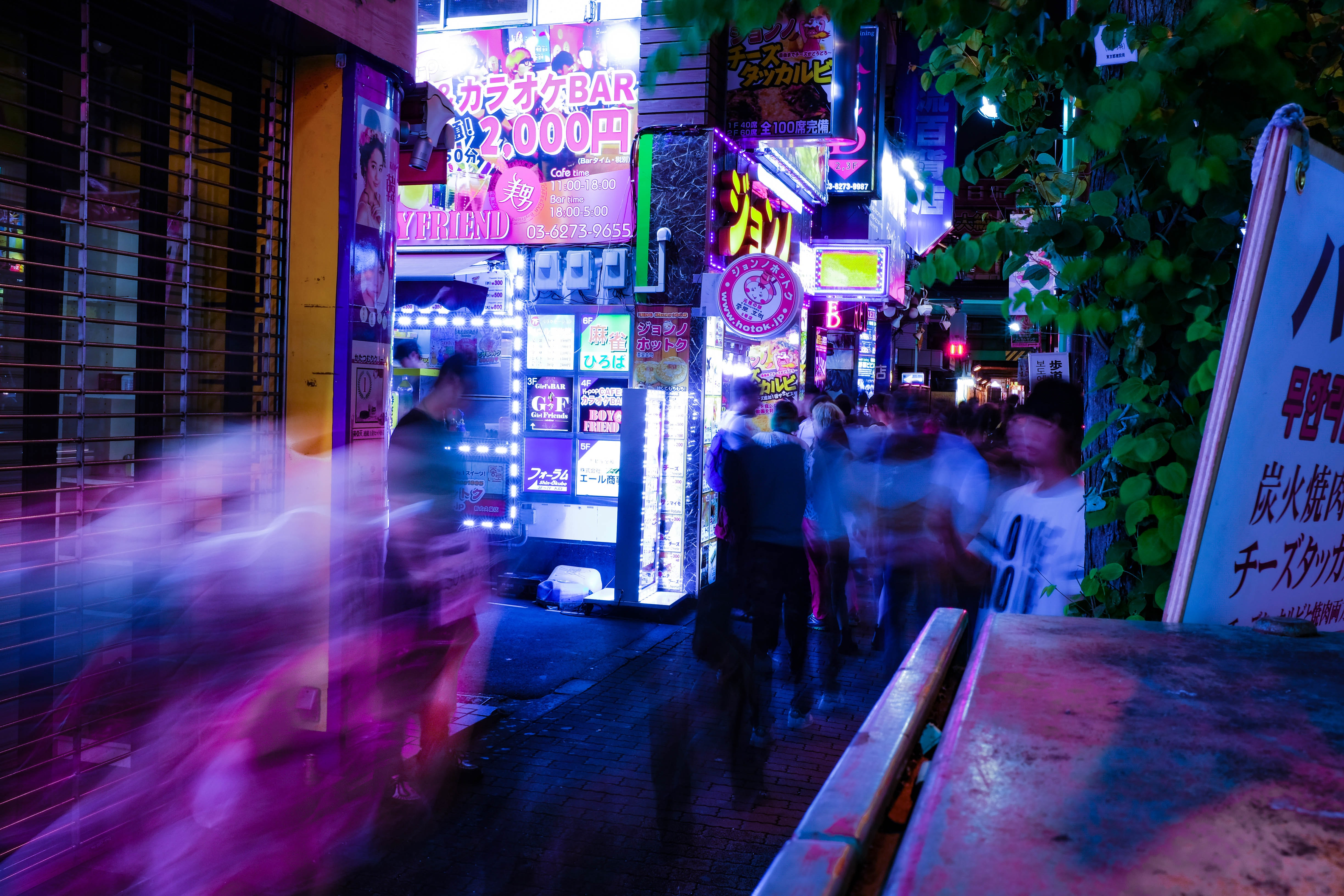 Long exposure of people walking in a city near bright shop signs
