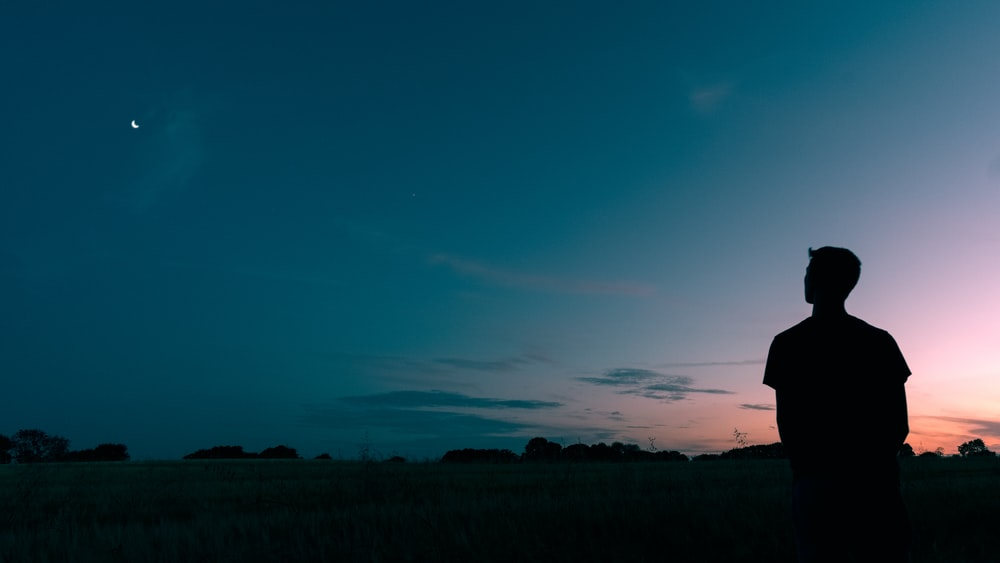 silhouette of man looking star during sunset