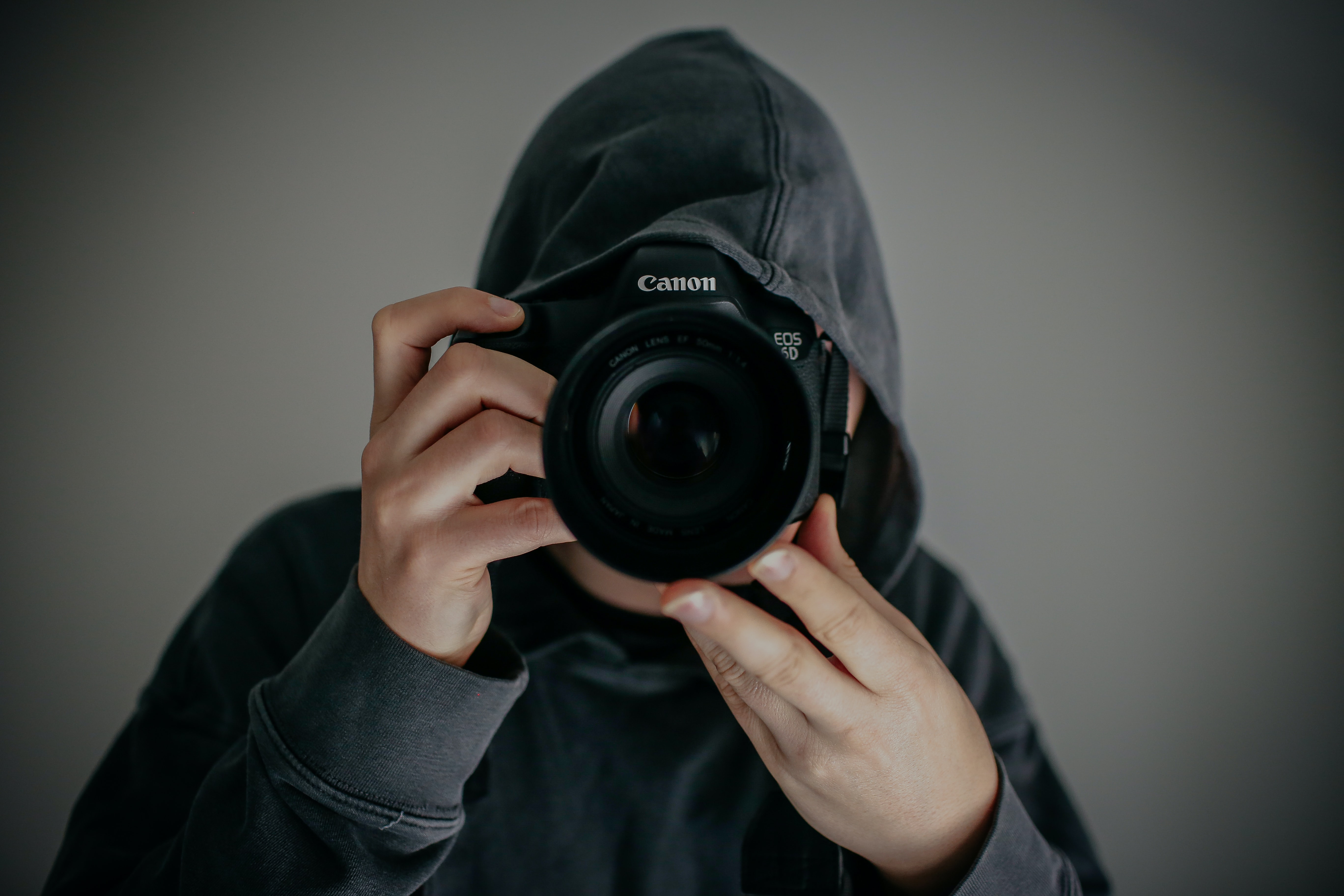 A guy in a hoodie taking a photo with a Canon camera