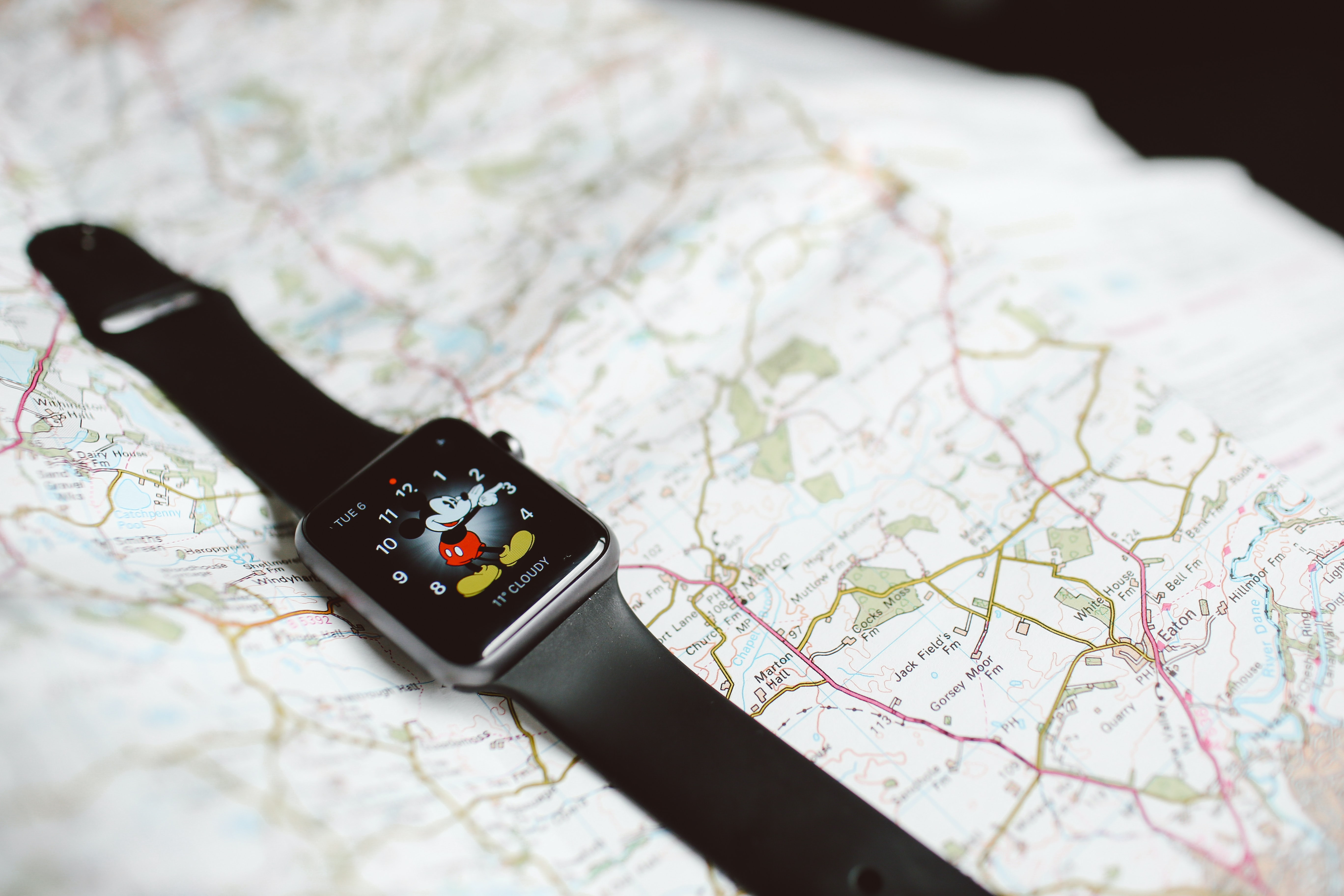 A smart watch with the Mickey theme pointing at 2:15 while resting on a map of Eaton