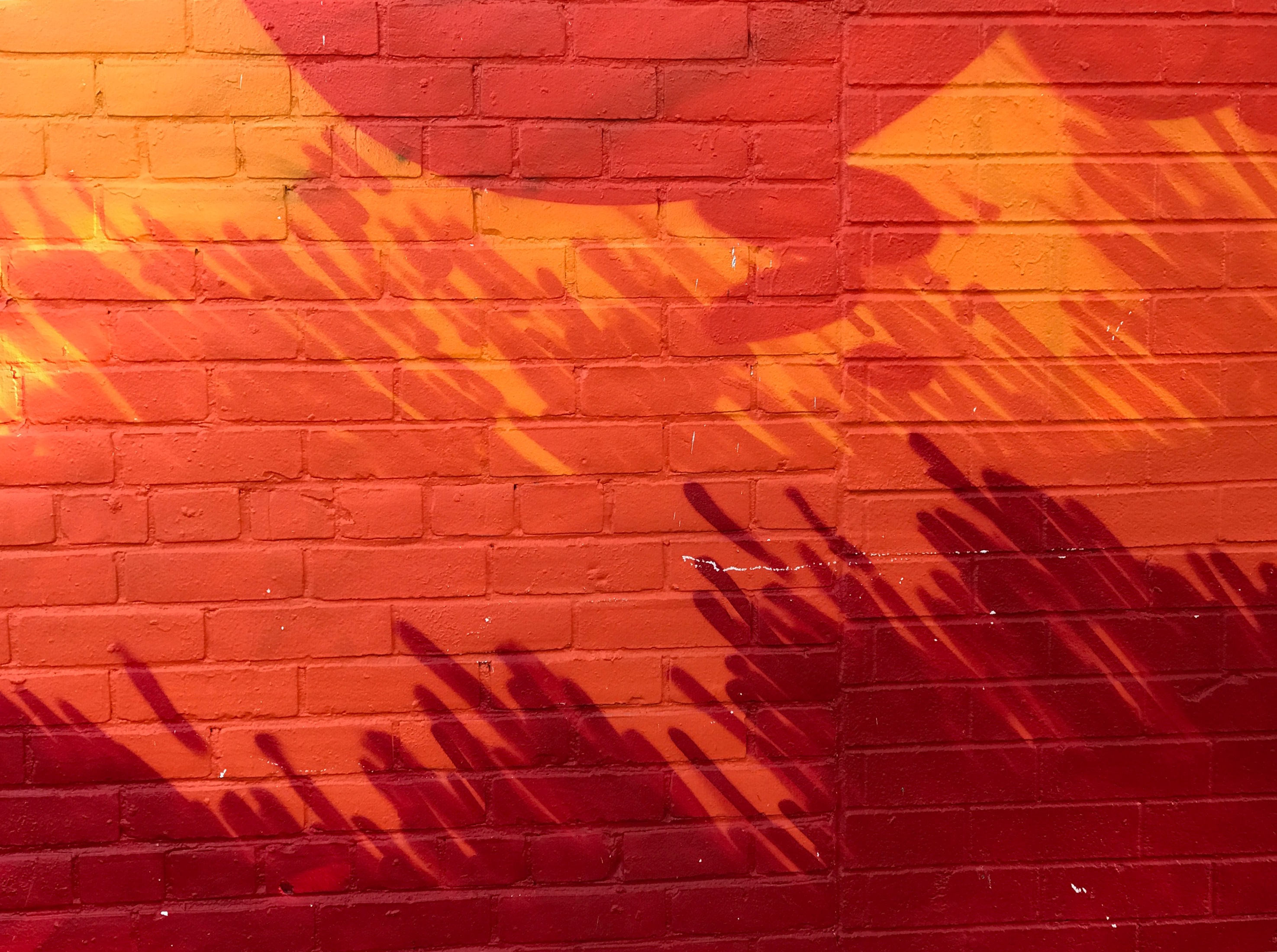Brick wall painted shades of red and orange