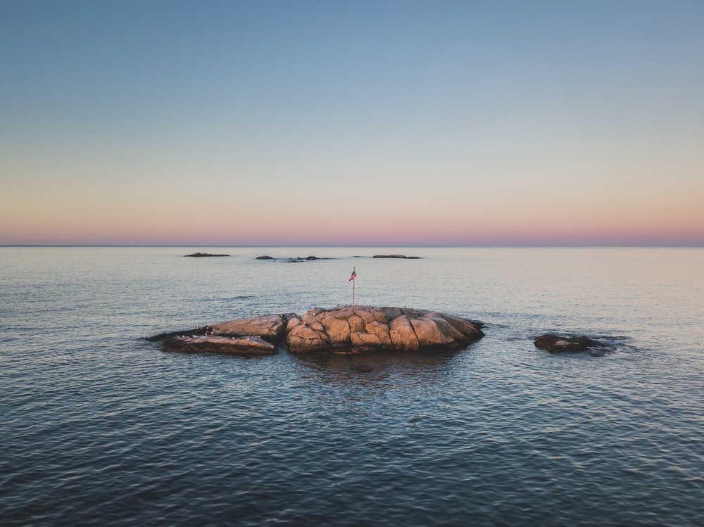 landscape photography of red flag on rock in the middle on ocean
